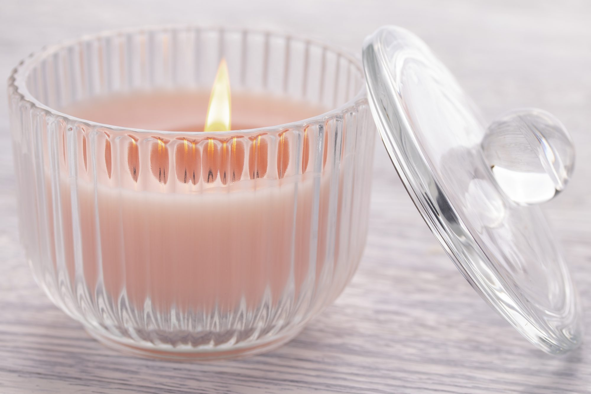 Pink candle burning in a glass beaker on an old white wooden table