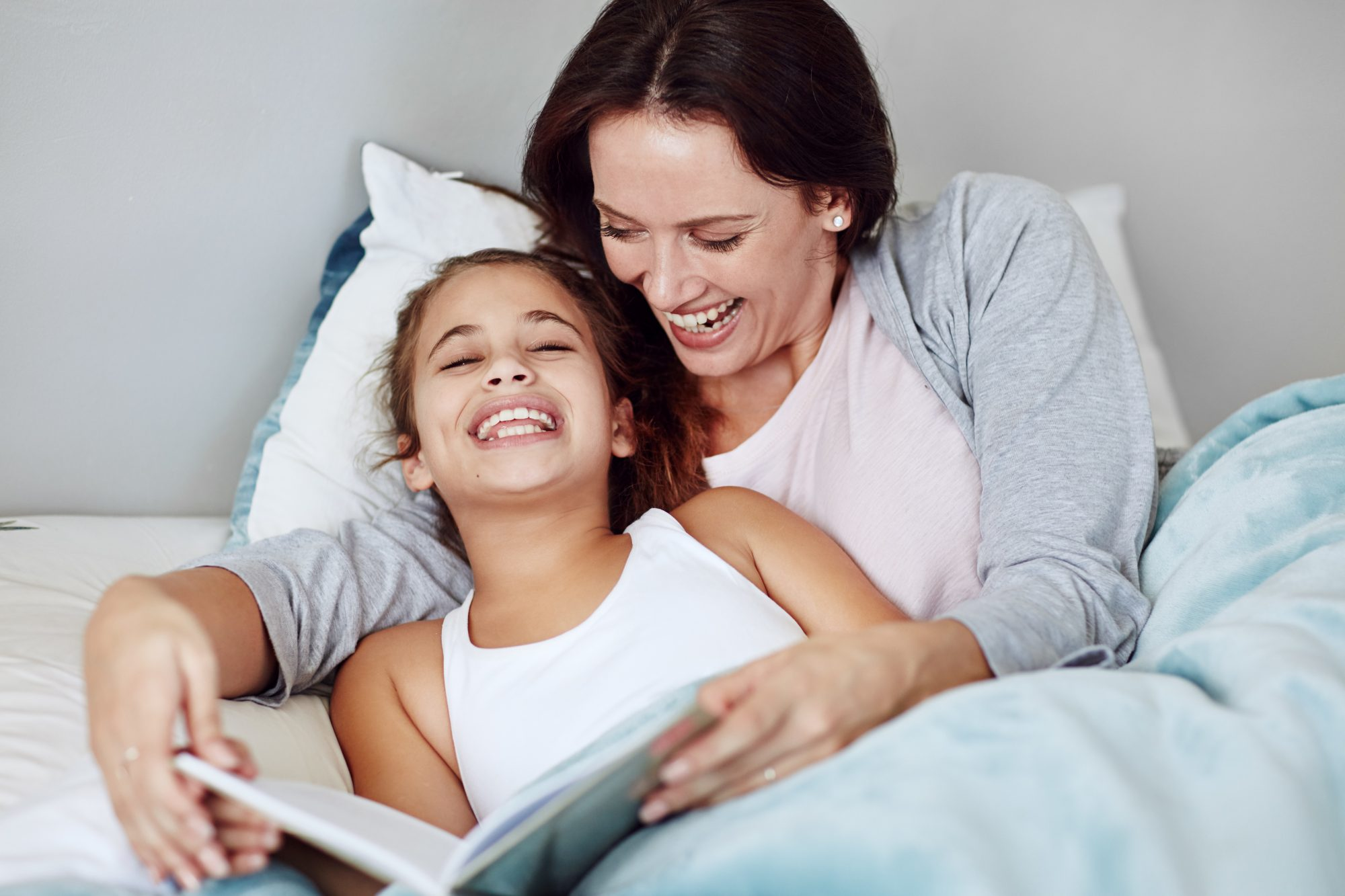 mother reading to daughter in bed