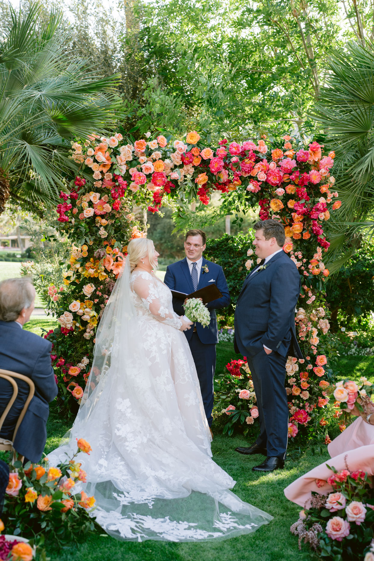 Bride and groom exchanging vows in floral arch