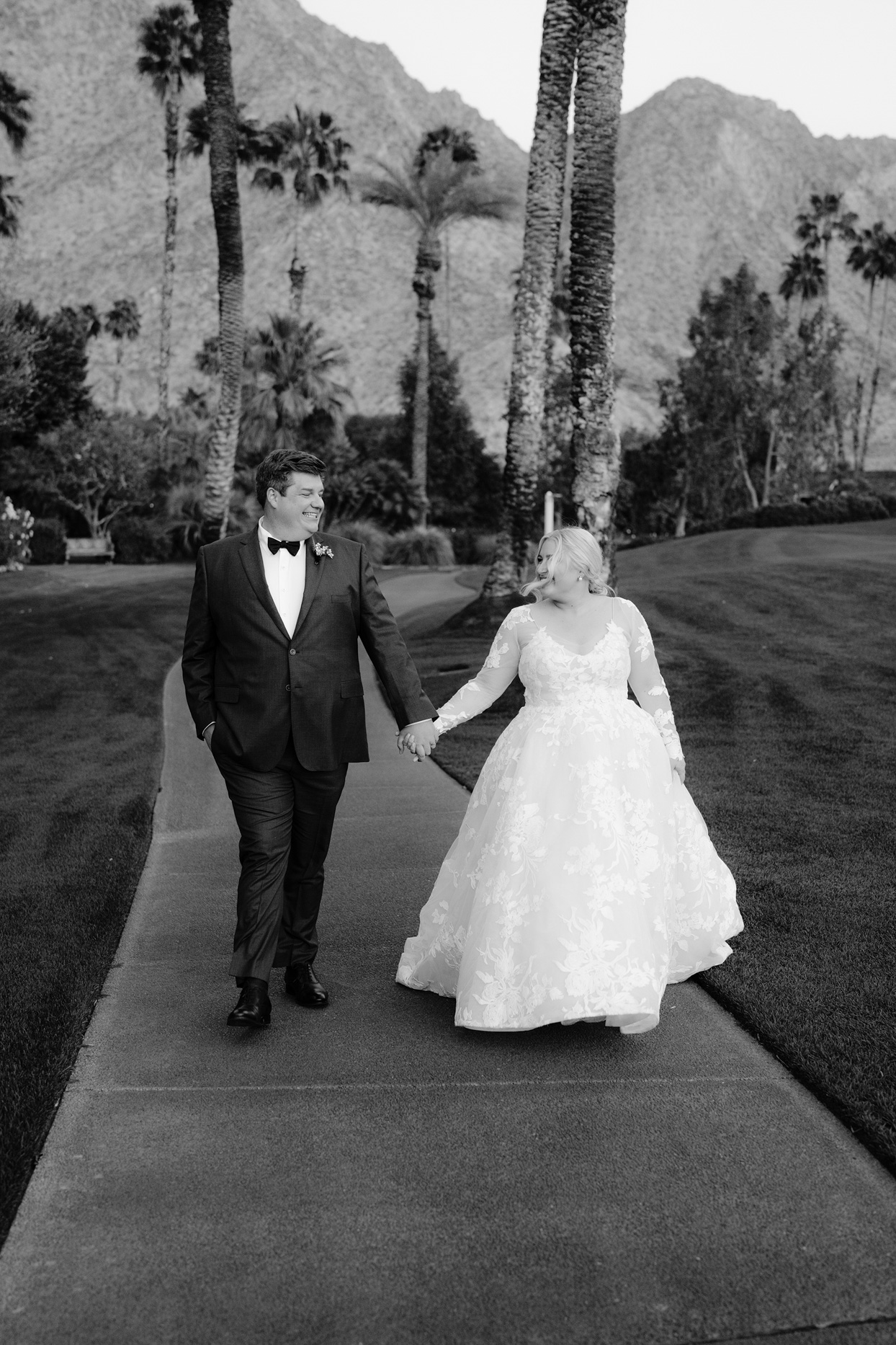 bride and groom walking on with palm trees