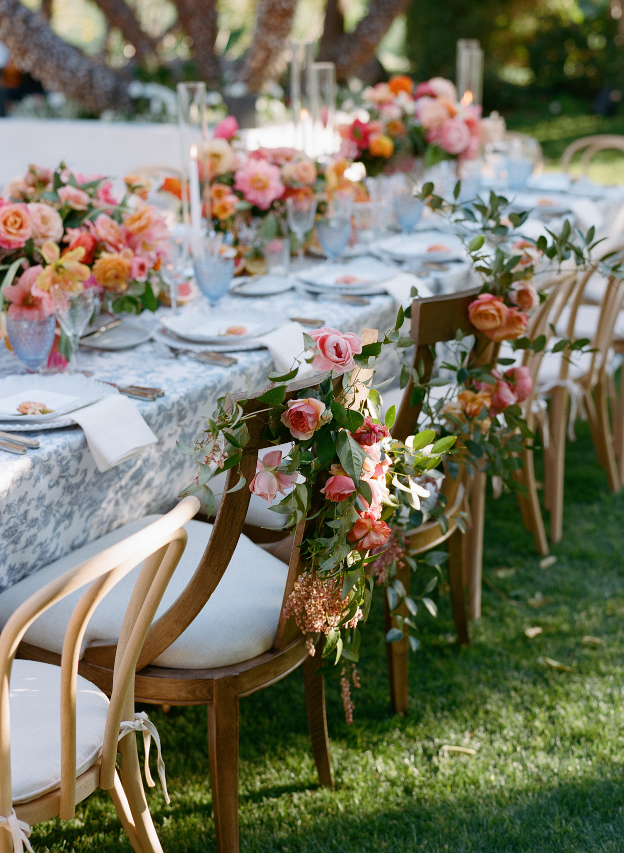 bride and groom reception chairs with floral arrangement