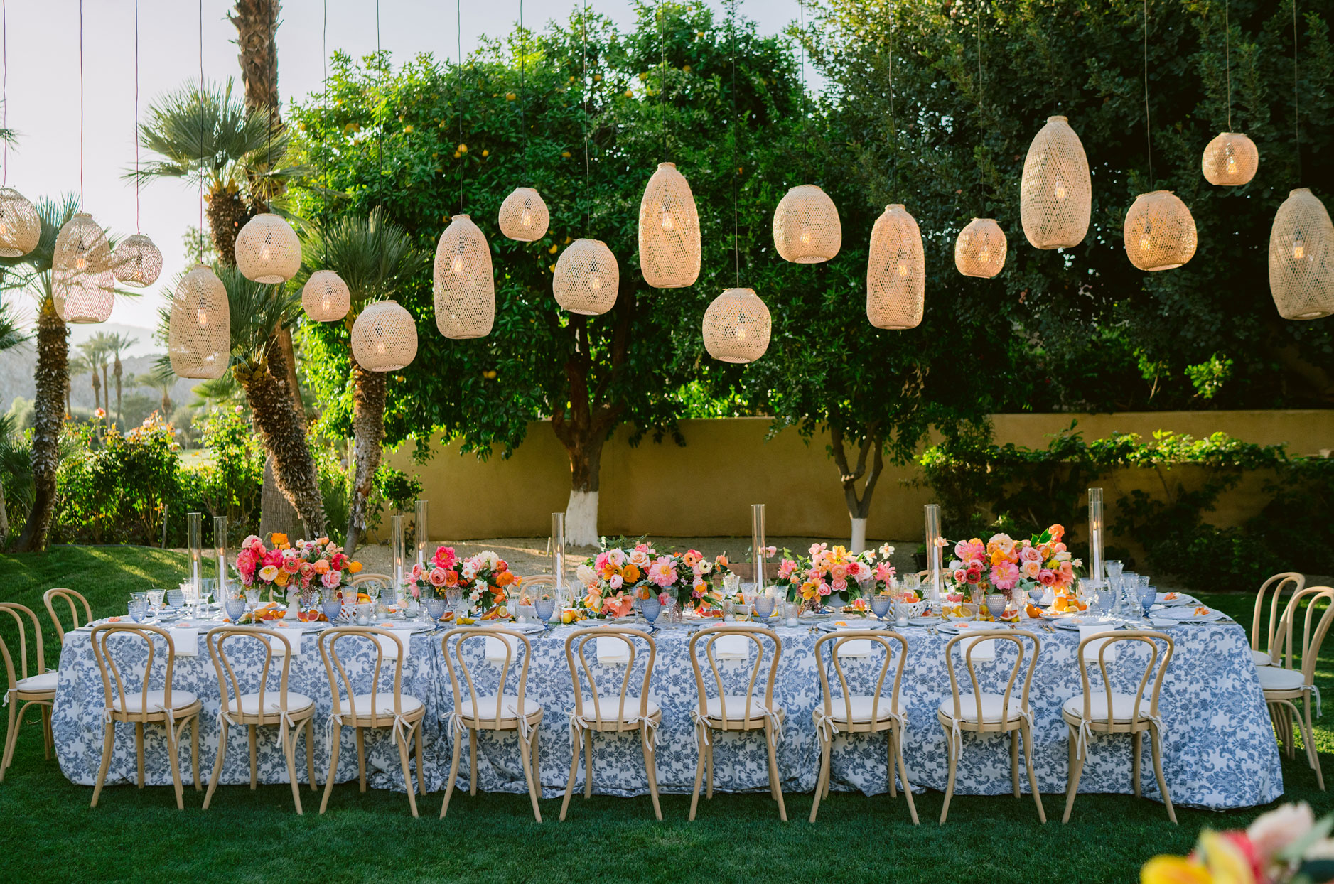 long reception table with hanging lanterns and flowers