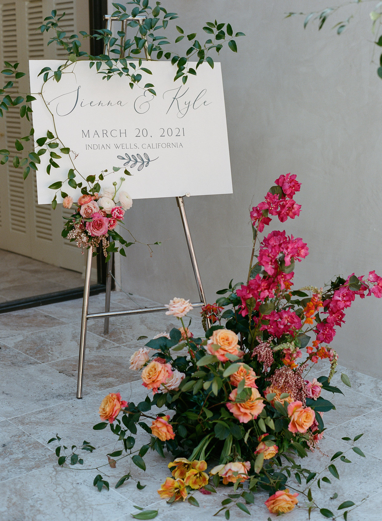 welcome sign on metal easel with flowers