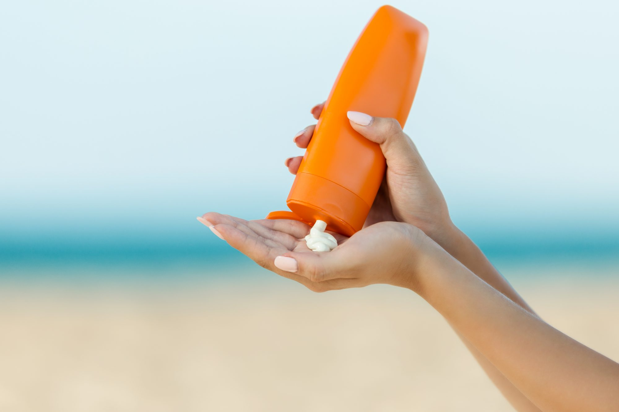 woman squeezing sunscreen in to hand