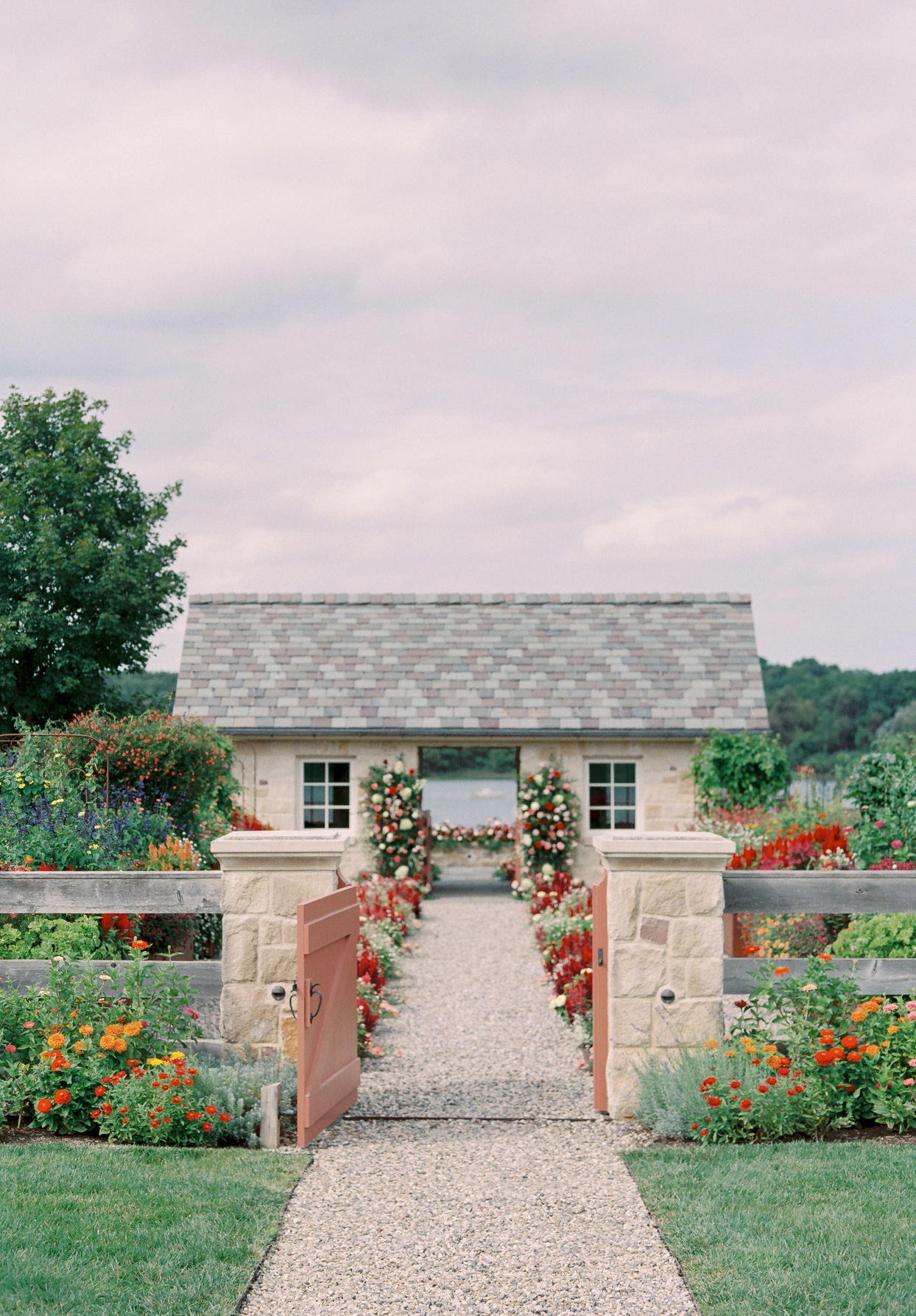 stone building and fence with red and white flowers for wedding