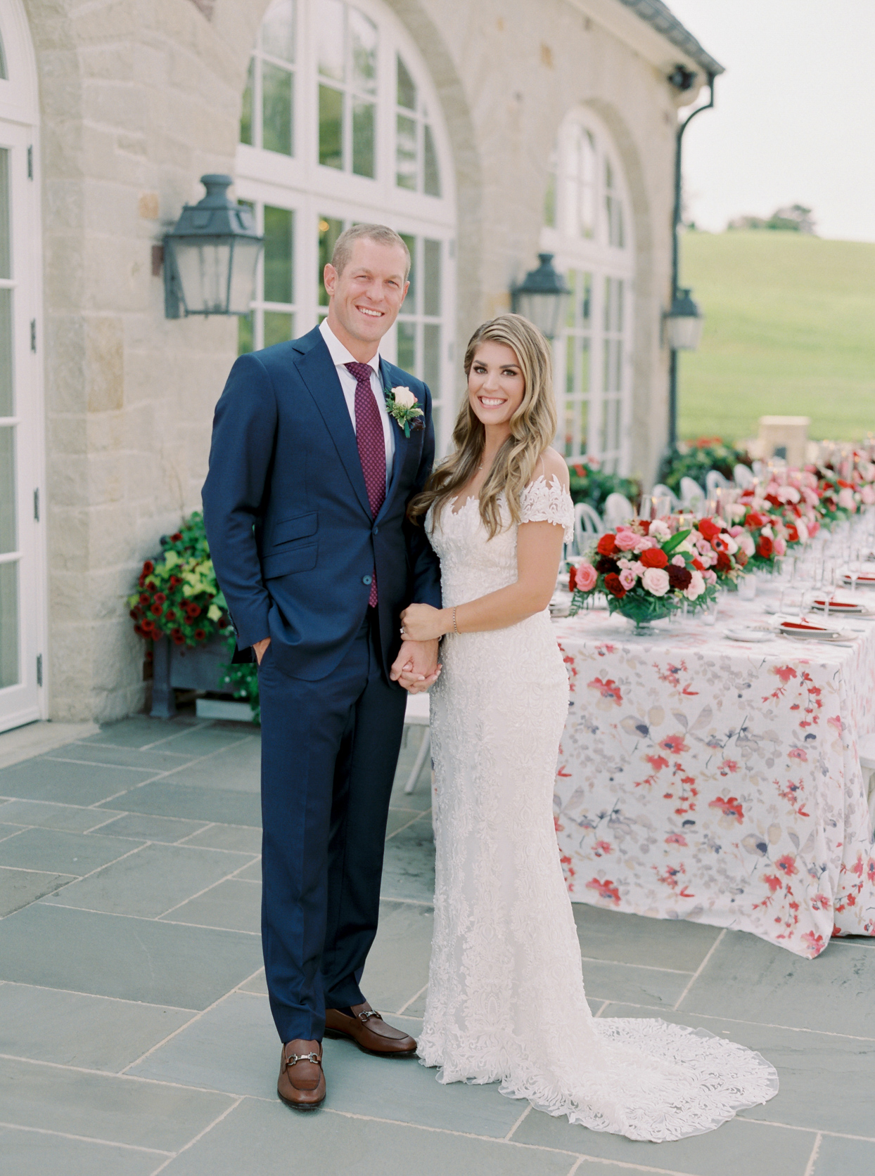 bride and groom standing beside floral table