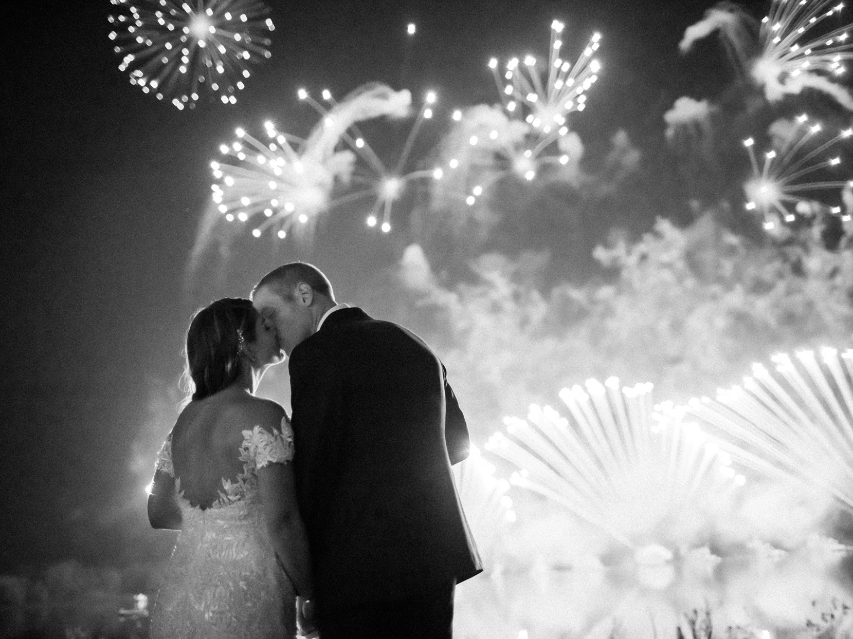 bride and groom kissing with fireworks