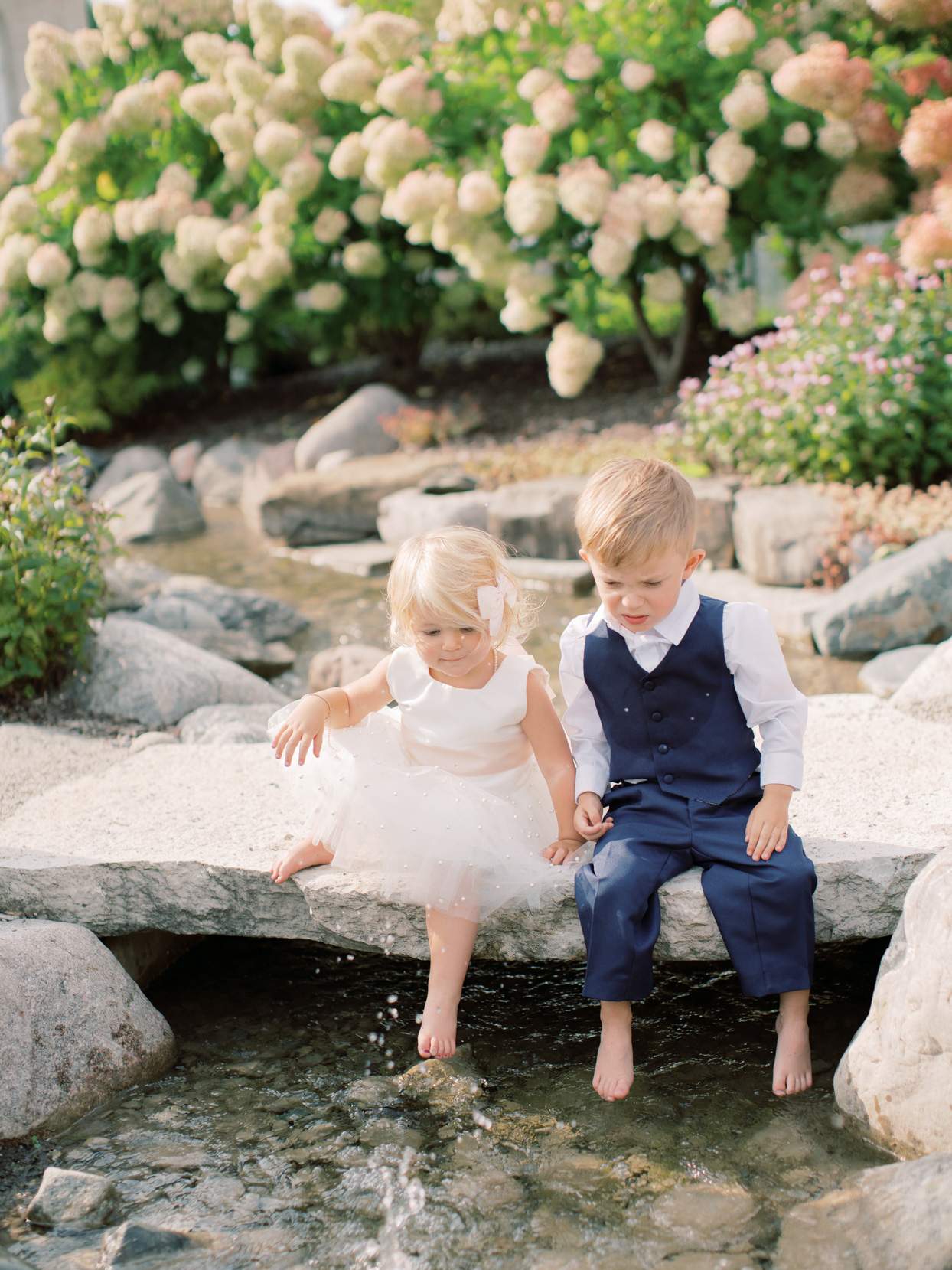 children with feet in water at wedding