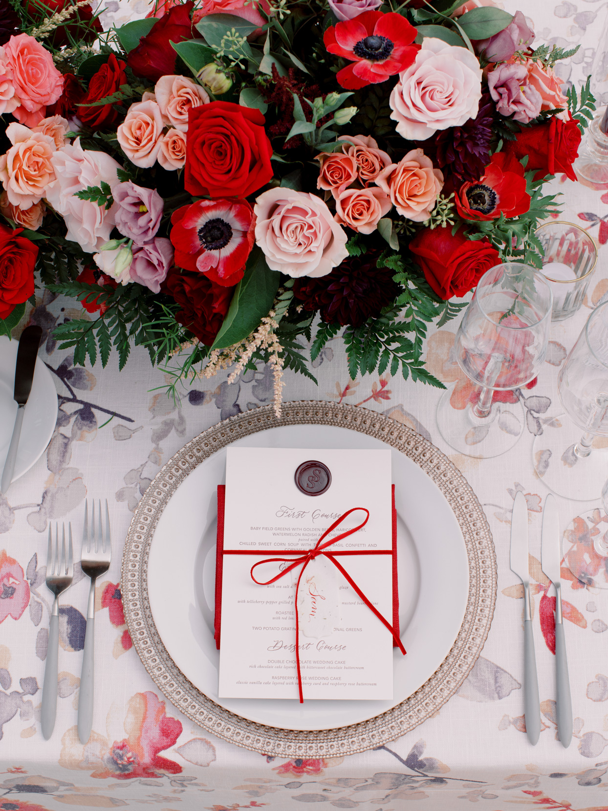 wedding place setting with red and white flowers