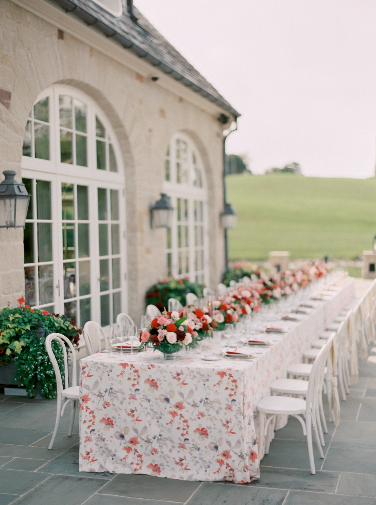 outdoor wedding reception table with floral tablecloth