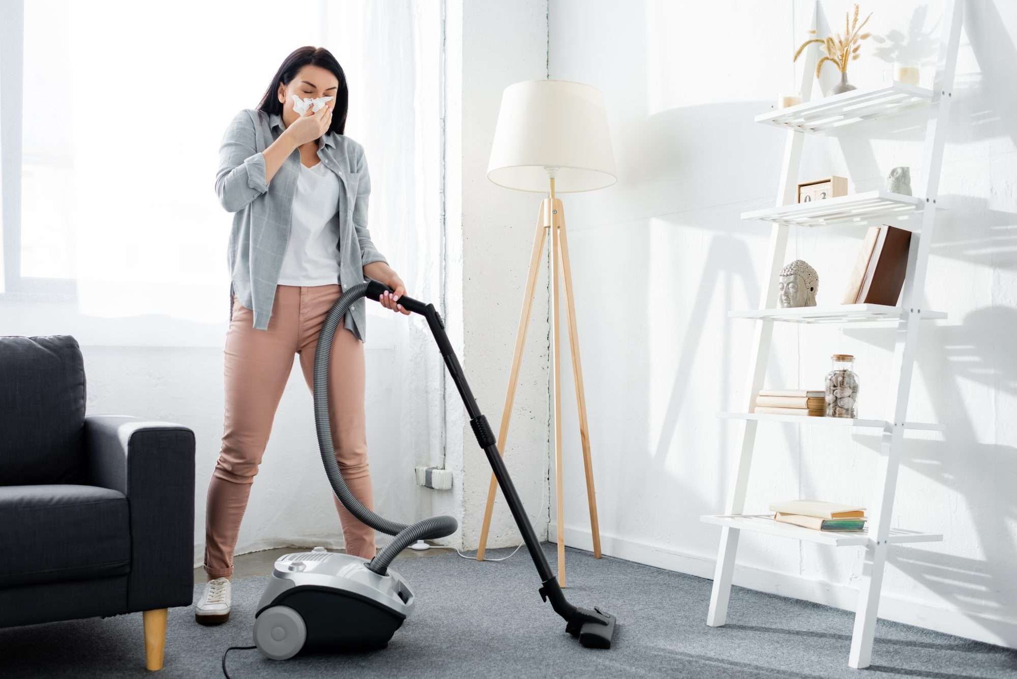 woman covering mouth with napkin and cleaning modern living room with vacuum cleaner