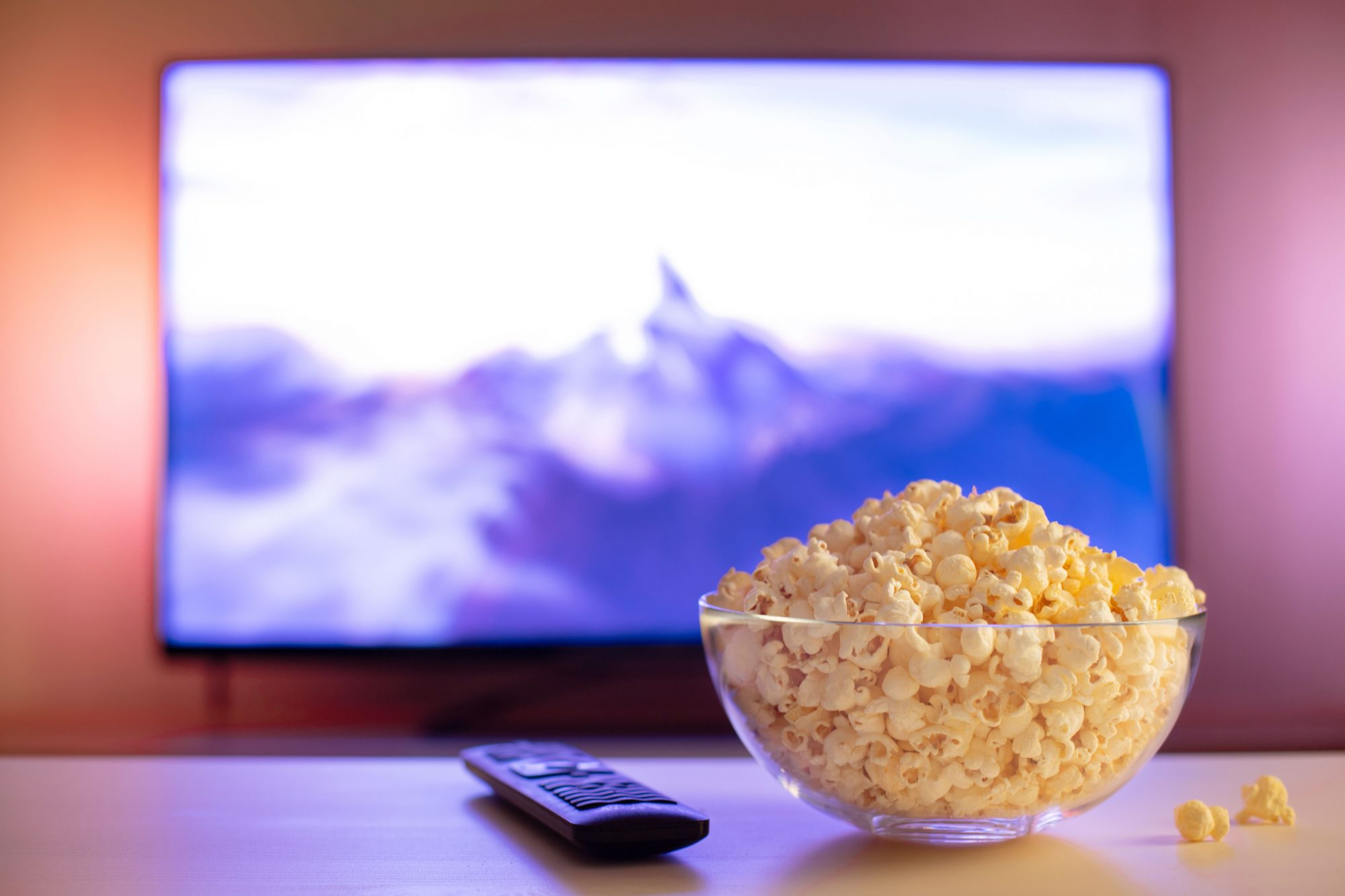 glass bowl of popcorn and remote control