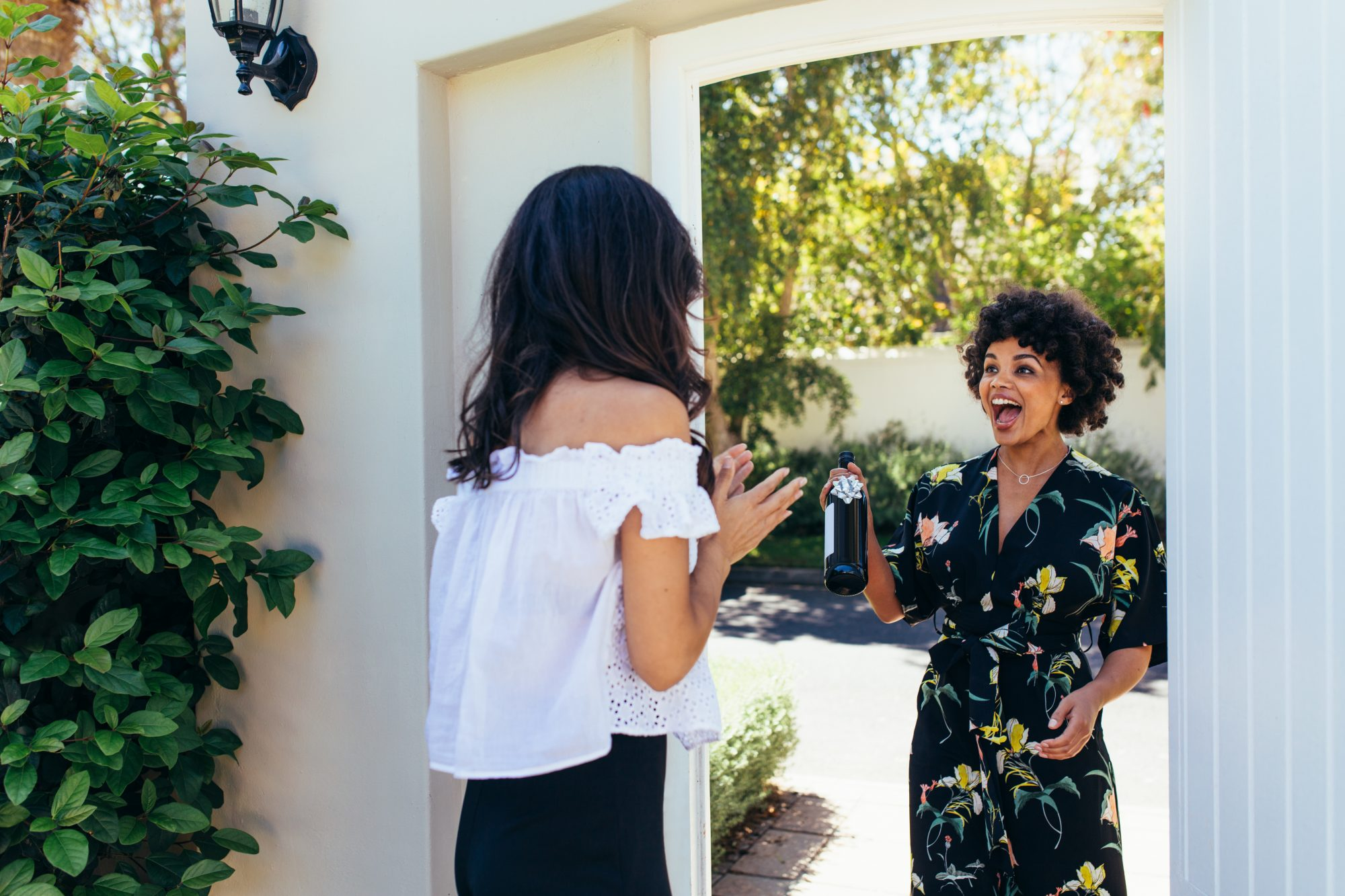 Excited woman with wine bottle for housewarming party