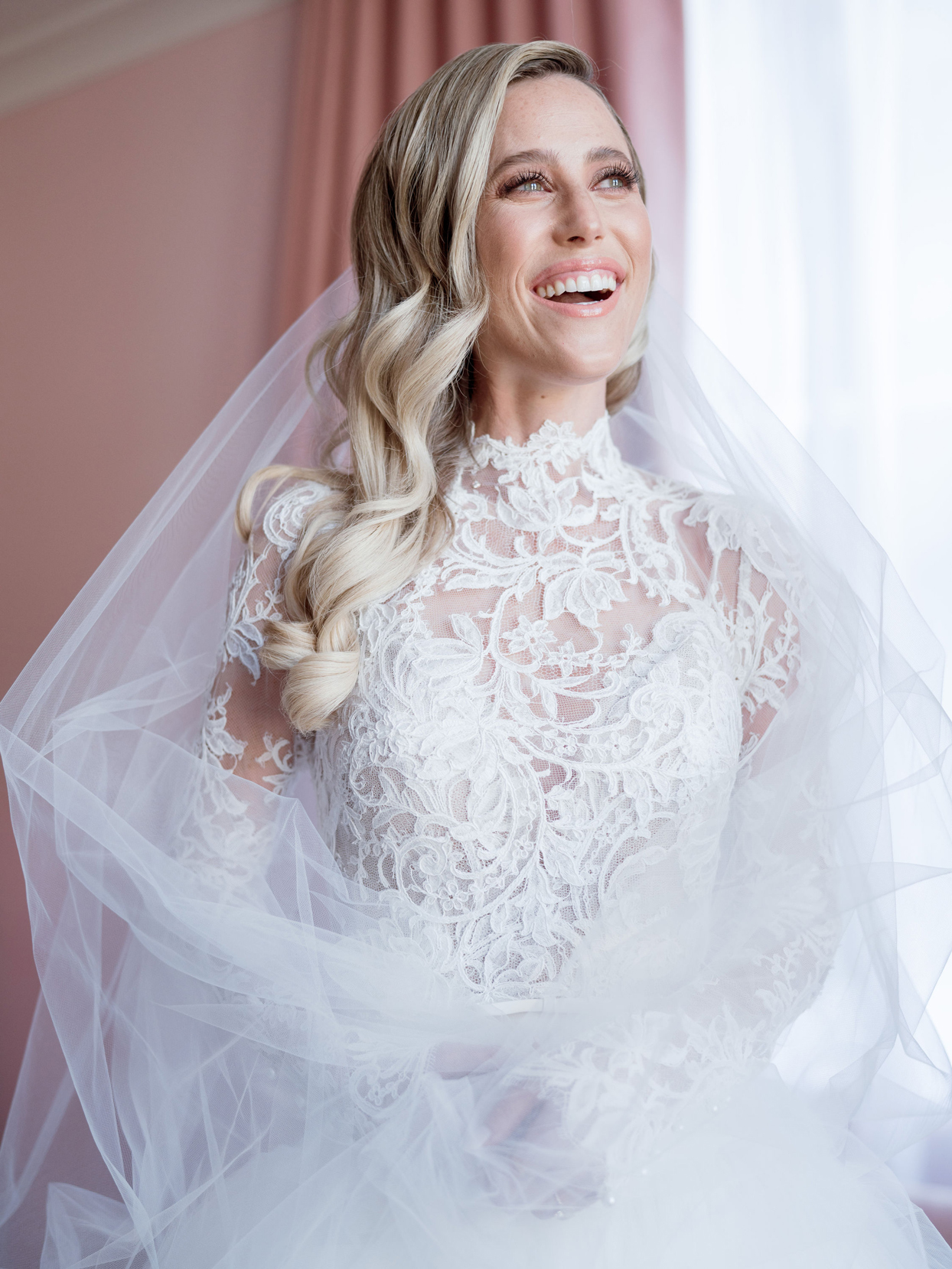 bride wearing high neck long sleeve gown laughing