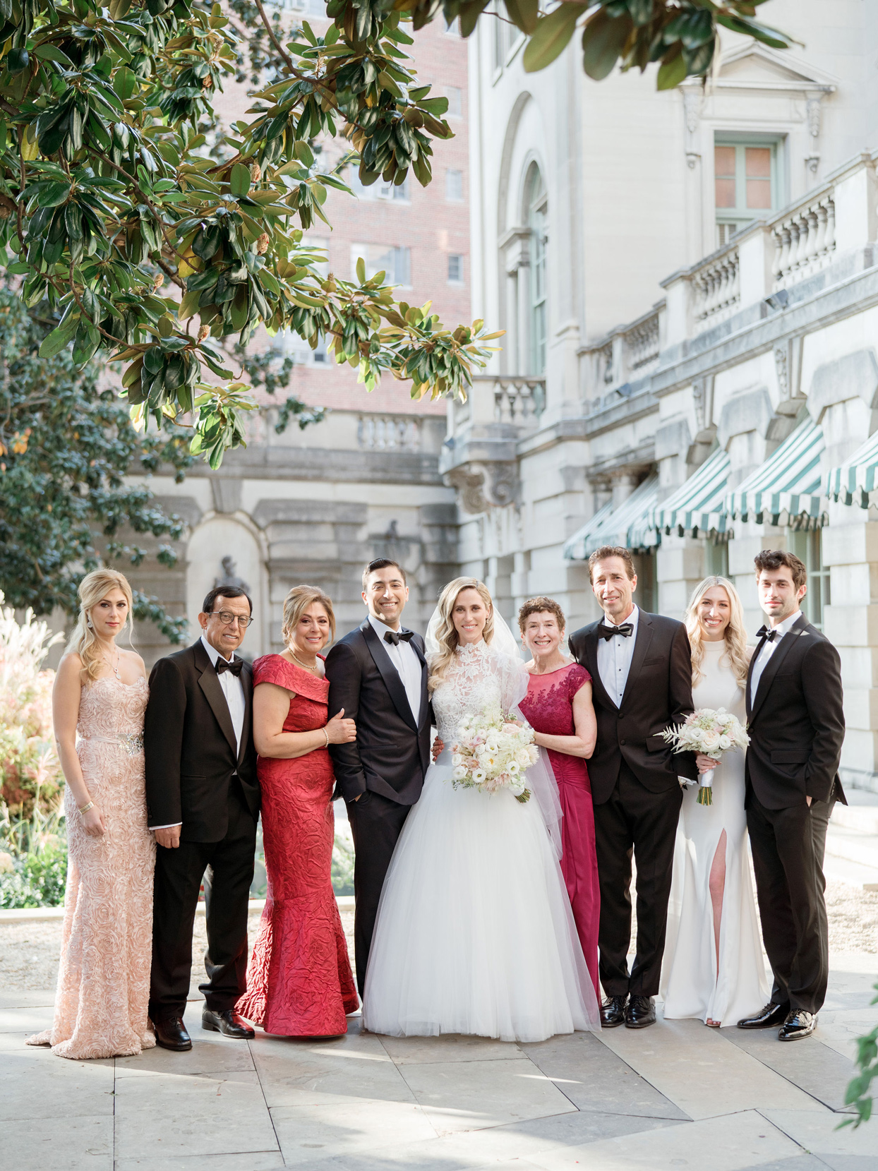 bride and groom posing with family wedding party