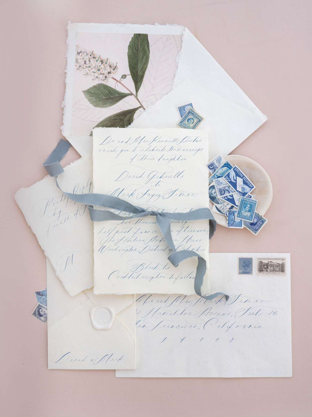 wedding invitation suite with handwritten calligraphy in light blue ink and raw-edge paper
