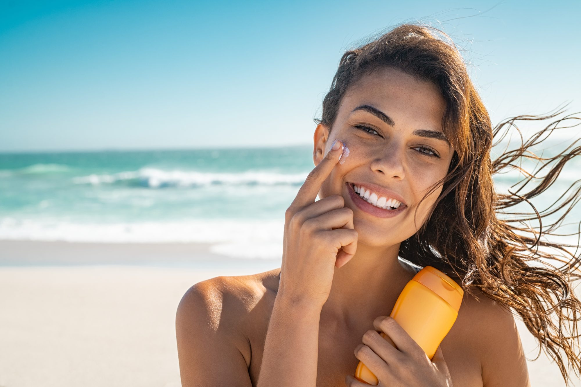 woman applying sunscreen to face at beach