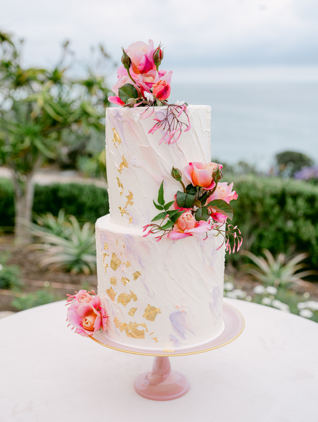 two tiered white frosted gold flake detail pink floral accent wedding cake