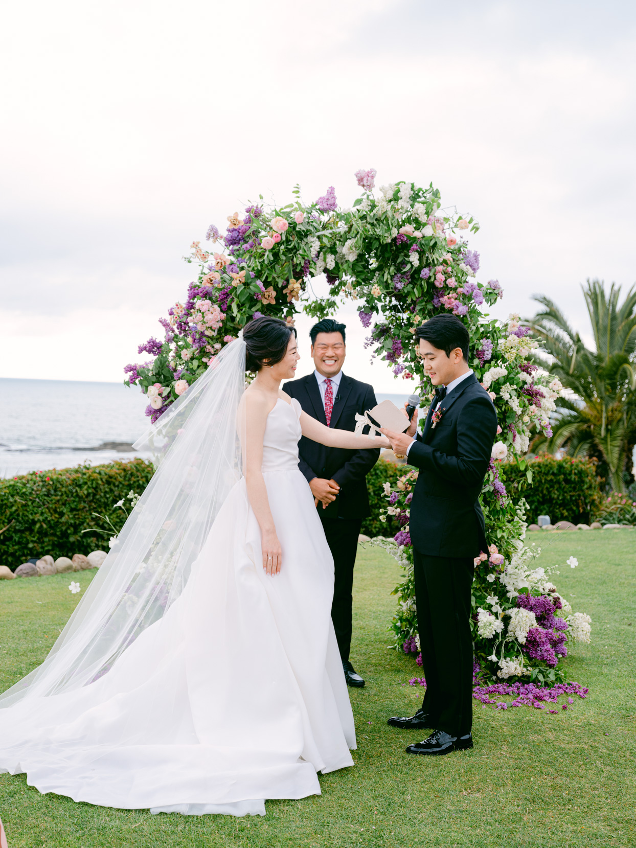 bride smiling while groom reads vows during ceremony
