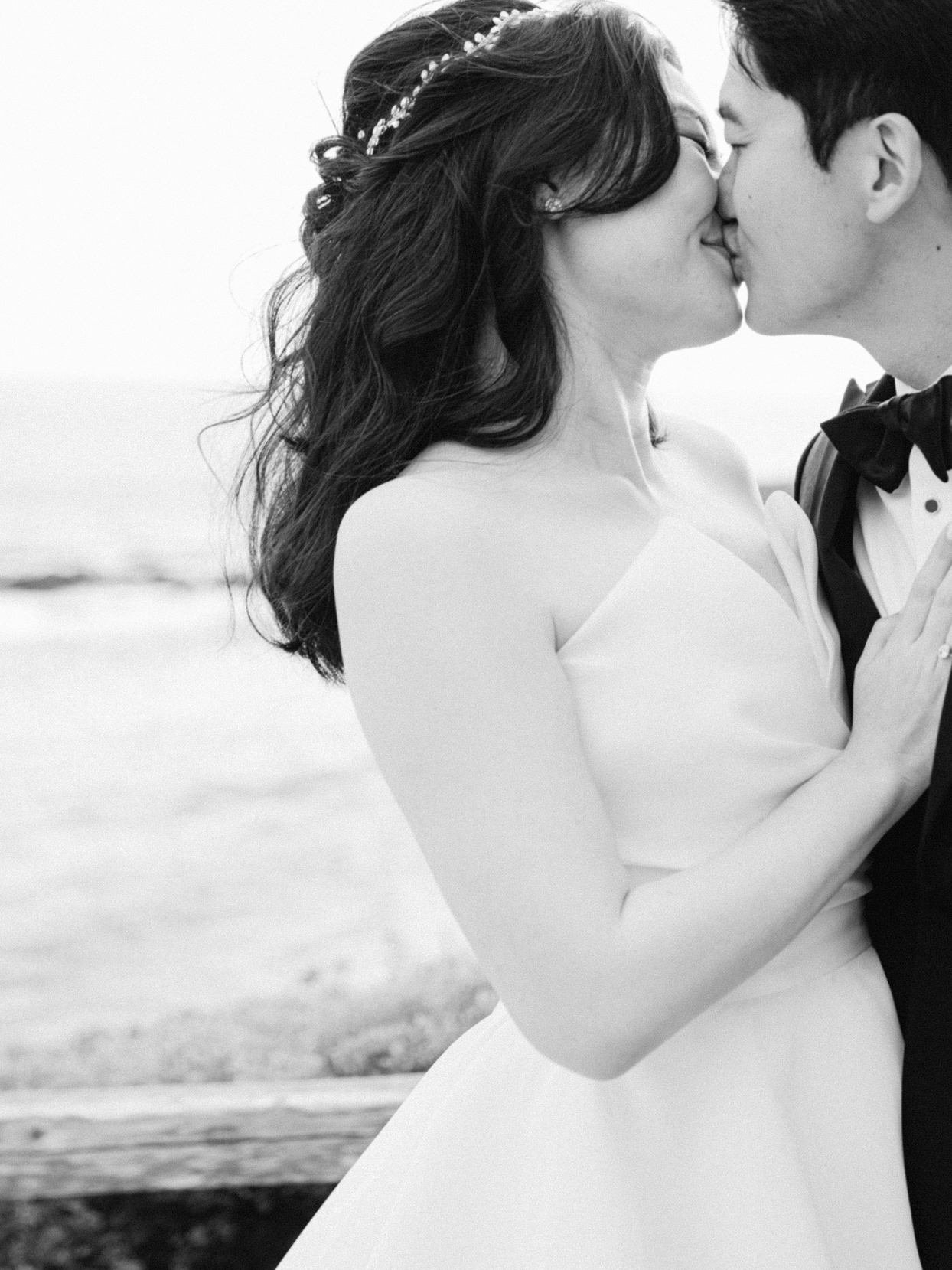 bride and groom embrace in kiss outside