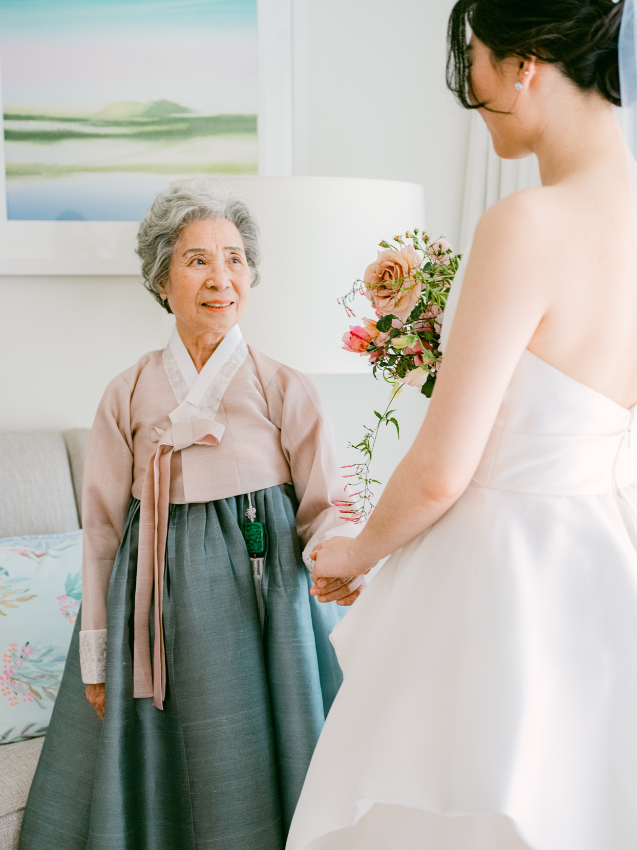 grandmother smiling at bride getting ready
