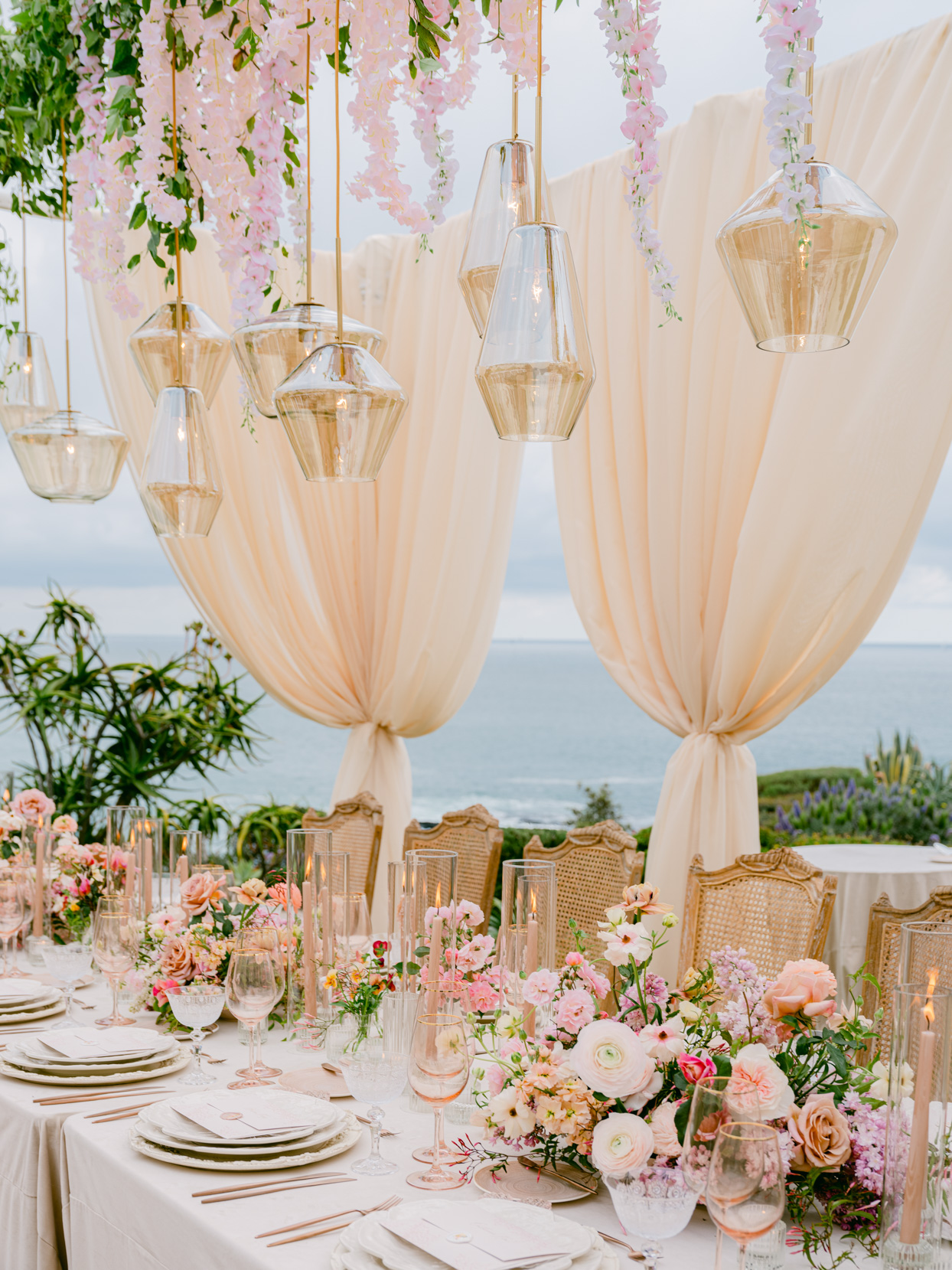 glass lighting fixtures over floral decor covered reception table