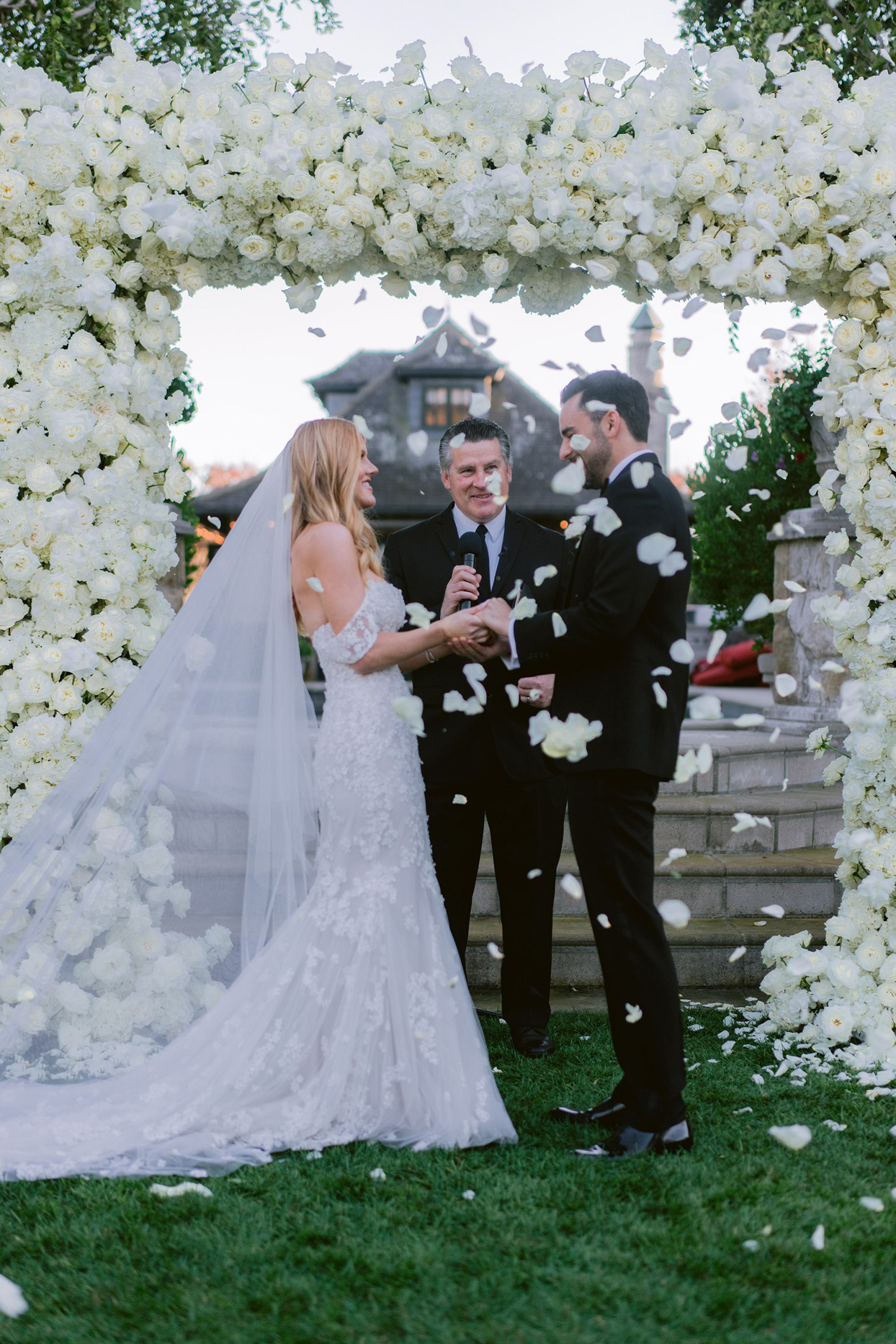 bride and groom being showered in white petals during wedding ceremony