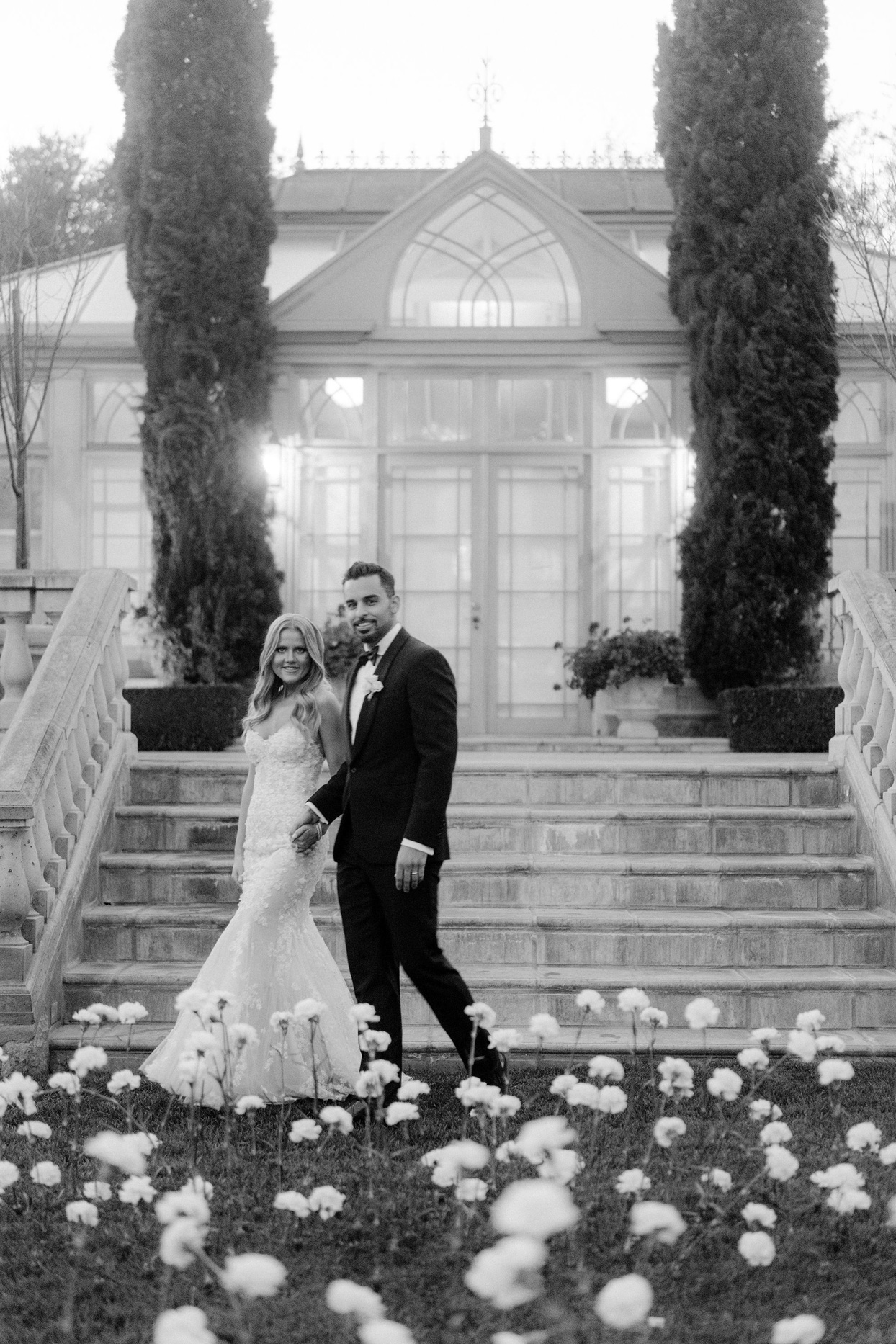 wedding couple walking at foot of stone staircase