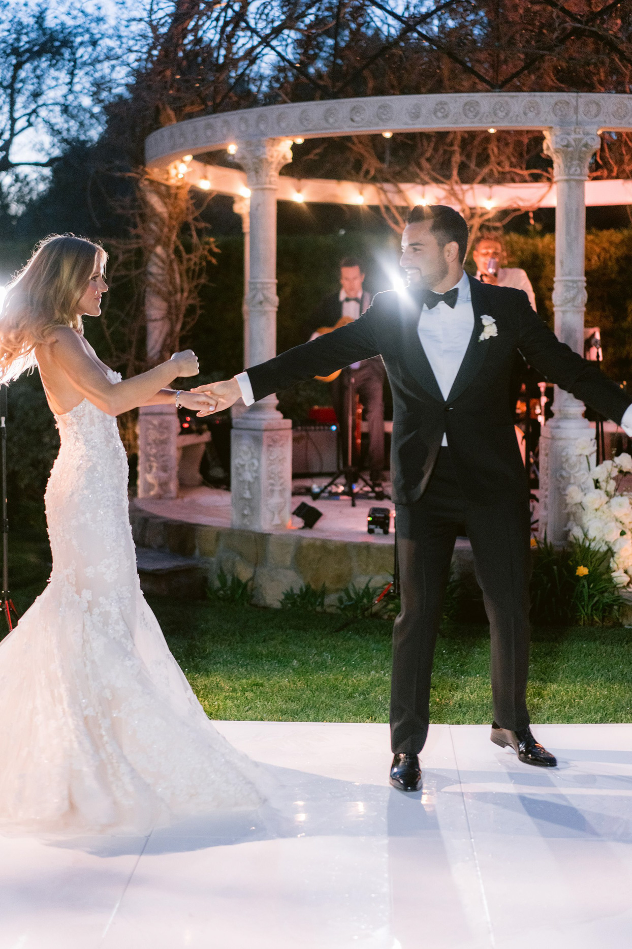 couple twirling for night time wedding reception dance