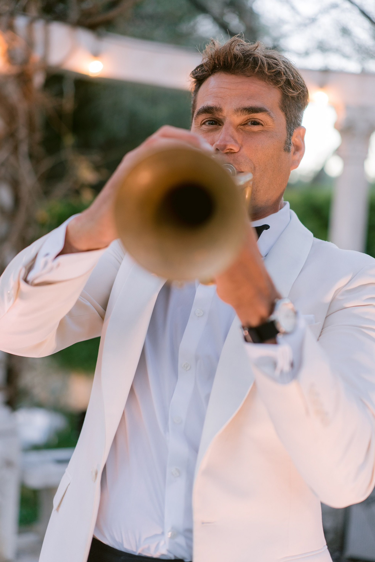 man in white suit playing trumpet for wedding