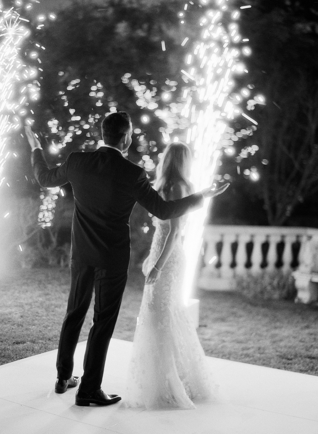 bride and groom watching wedding sparklers at night
