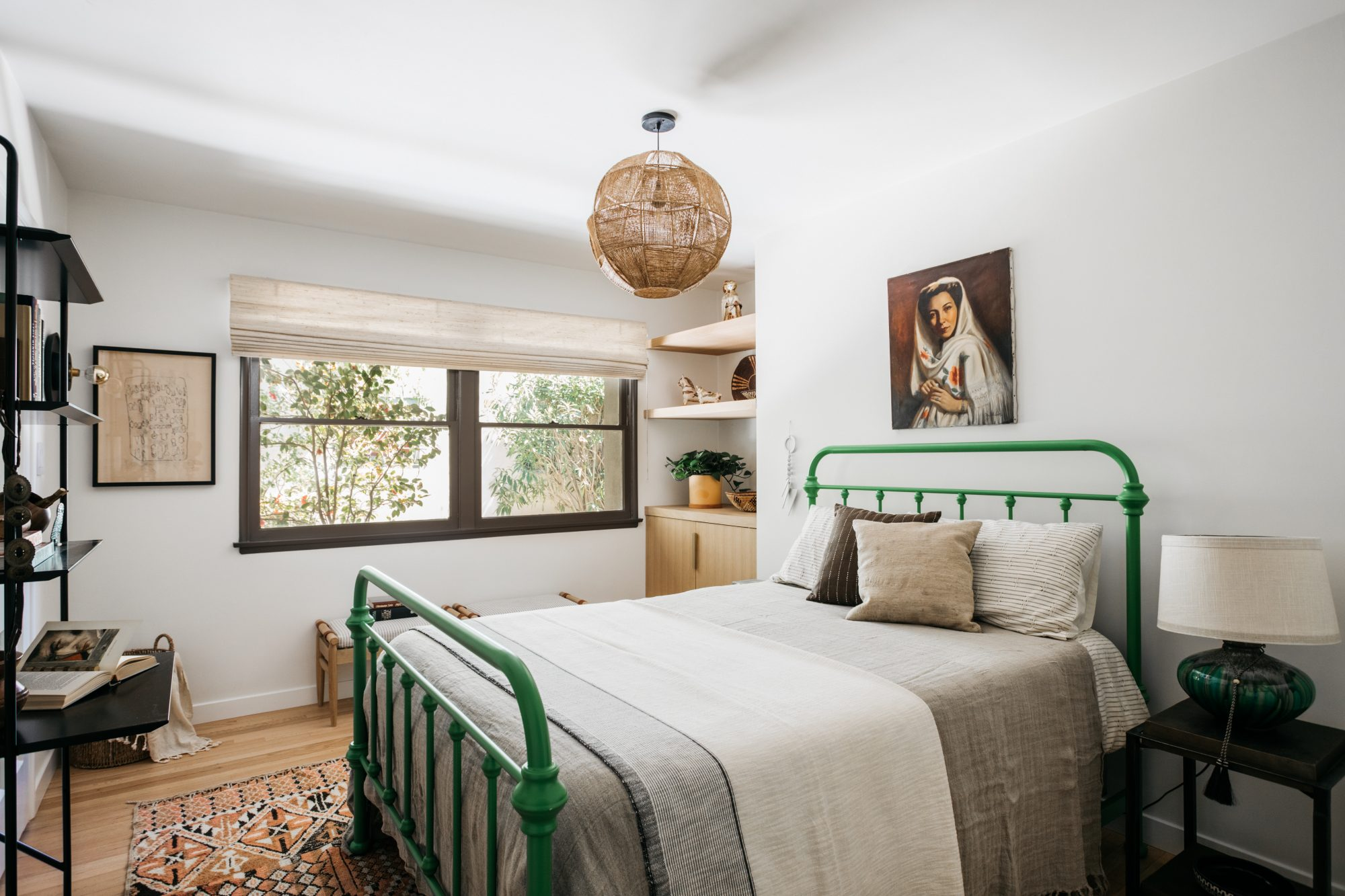 guest bedroom with green painted bedframe