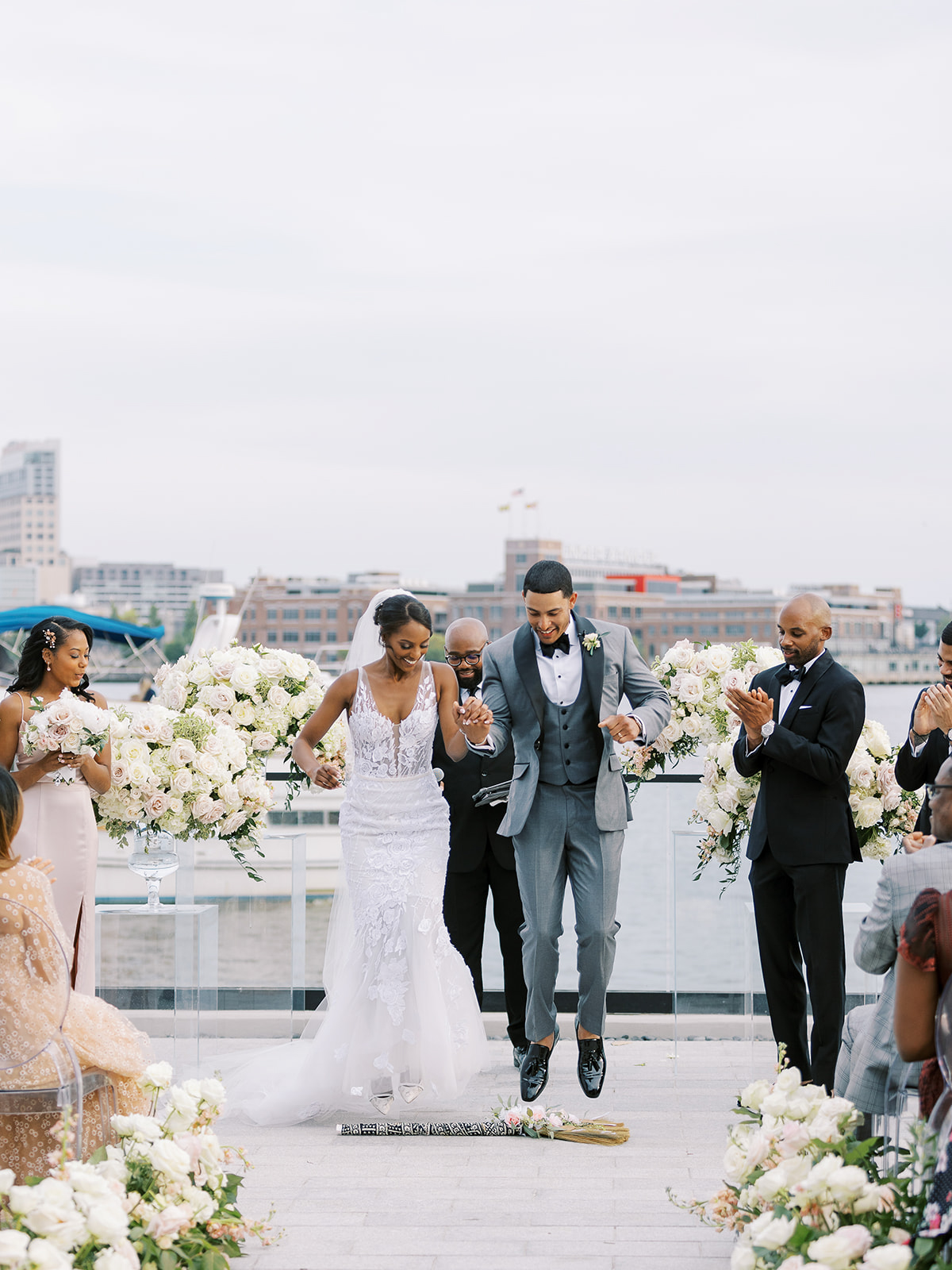 bride and groom jumping over broom