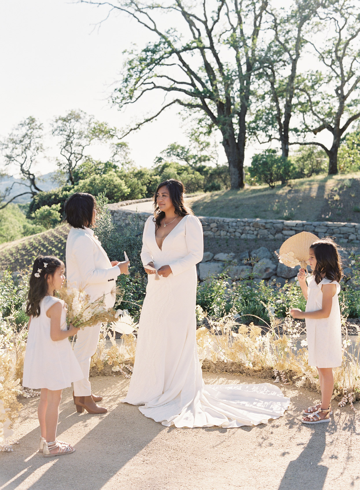 brides standing outdoors with daughters for vow renewal ceremony