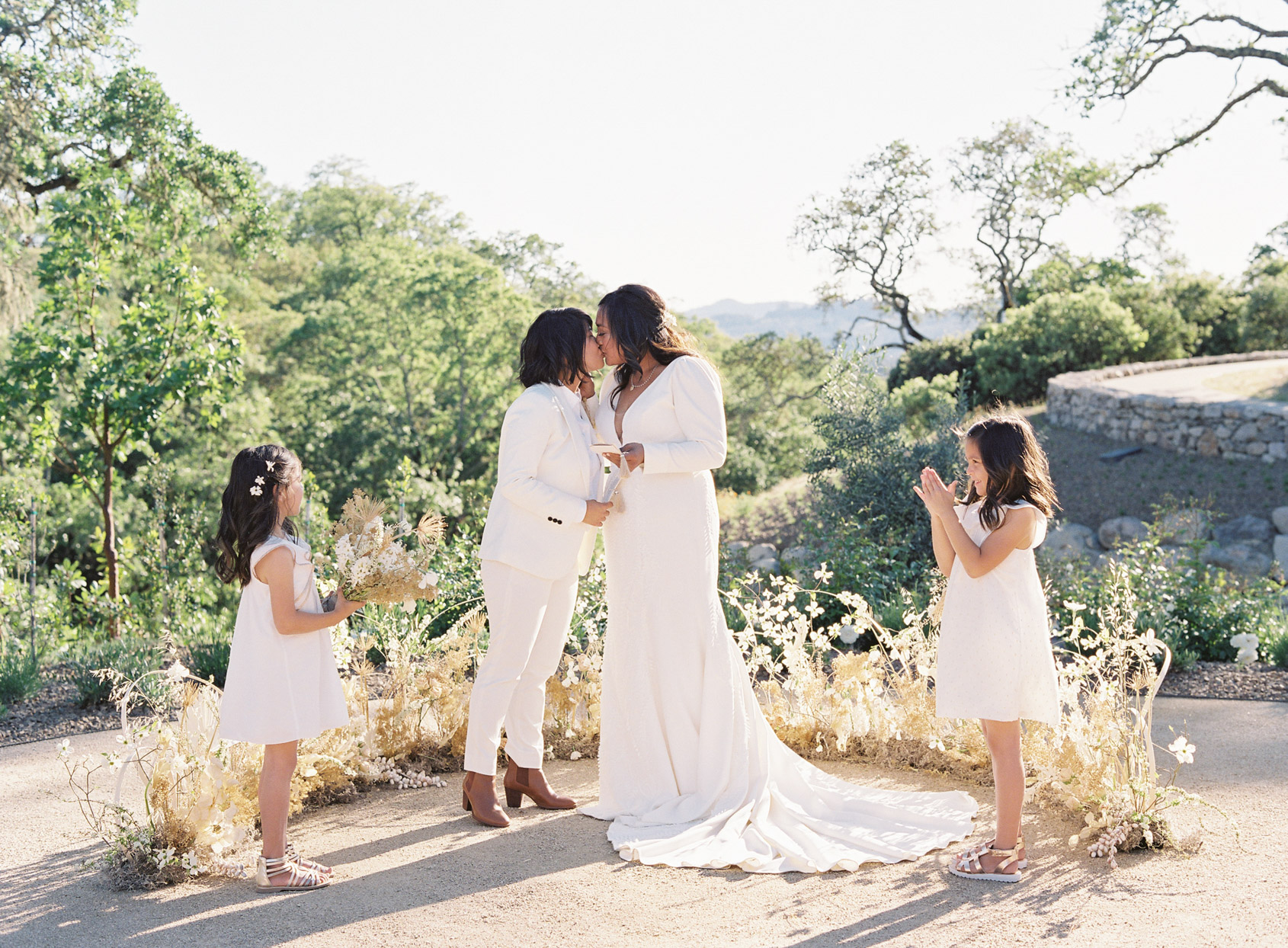 brides kissing during outdoor vow renewal