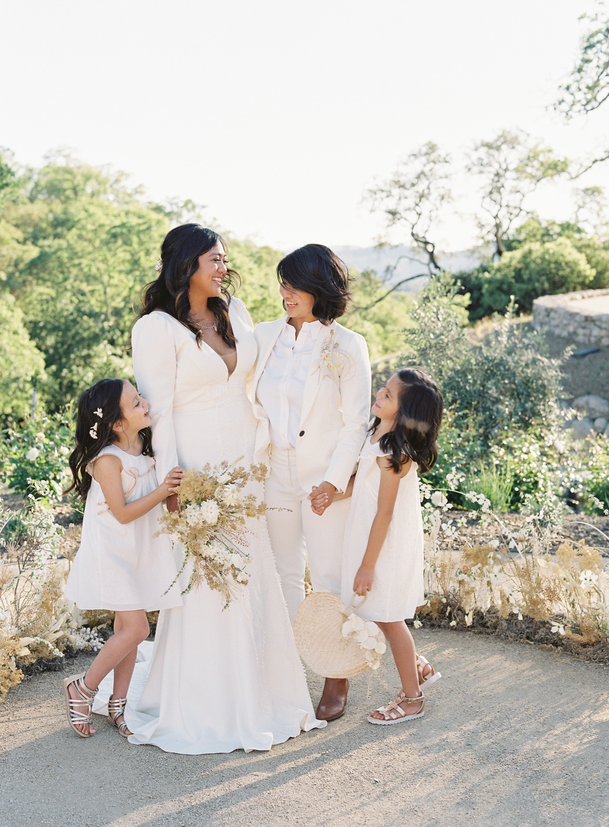 brides and daughters holding hands for outdoor portrait at vow renewal