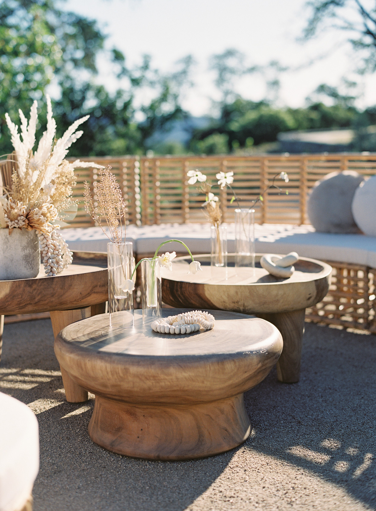 wooden tables with glasses of white flowers at vow renewal lounge