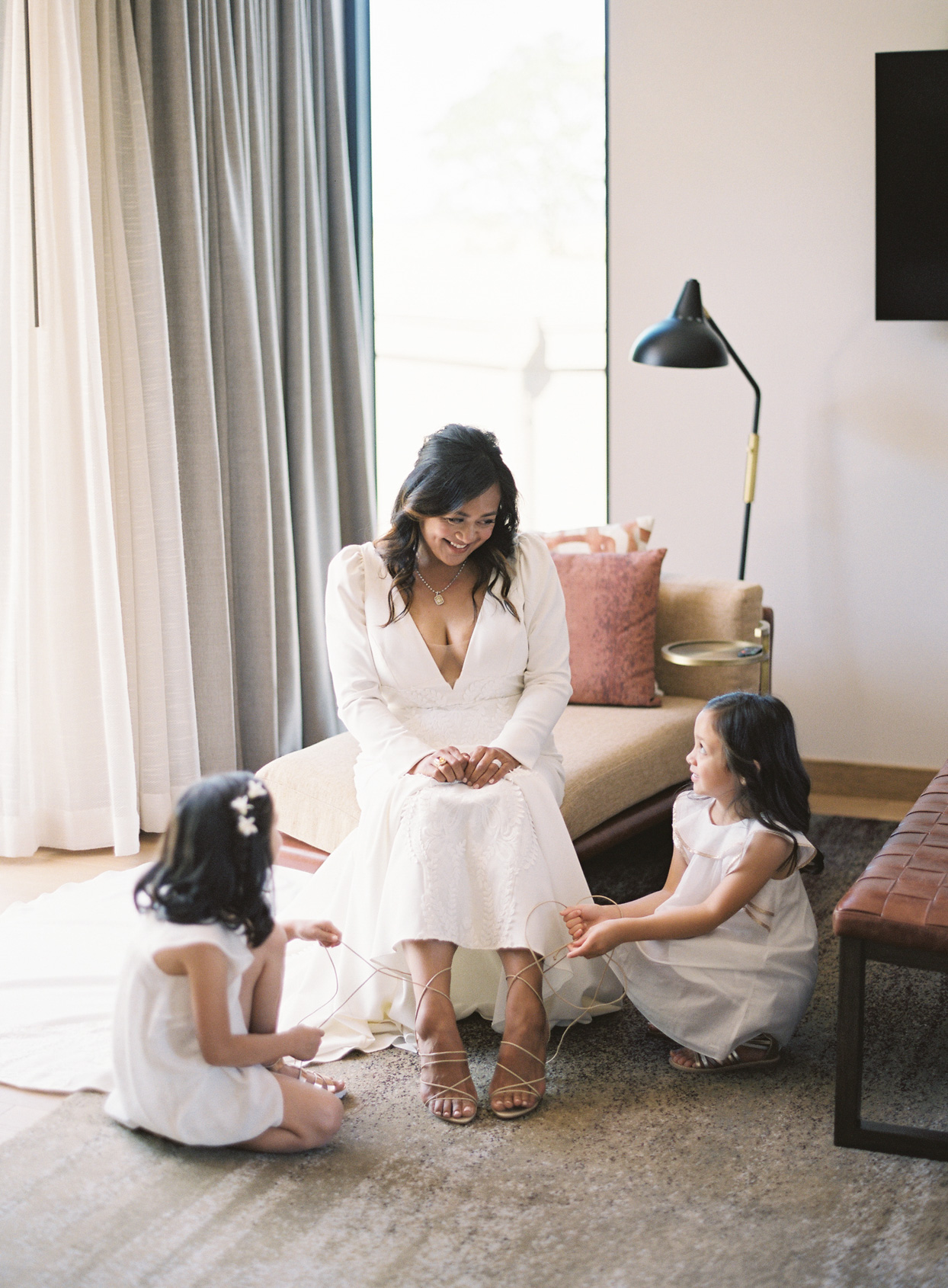 sarah in white dress with daughters strapping up her shoes