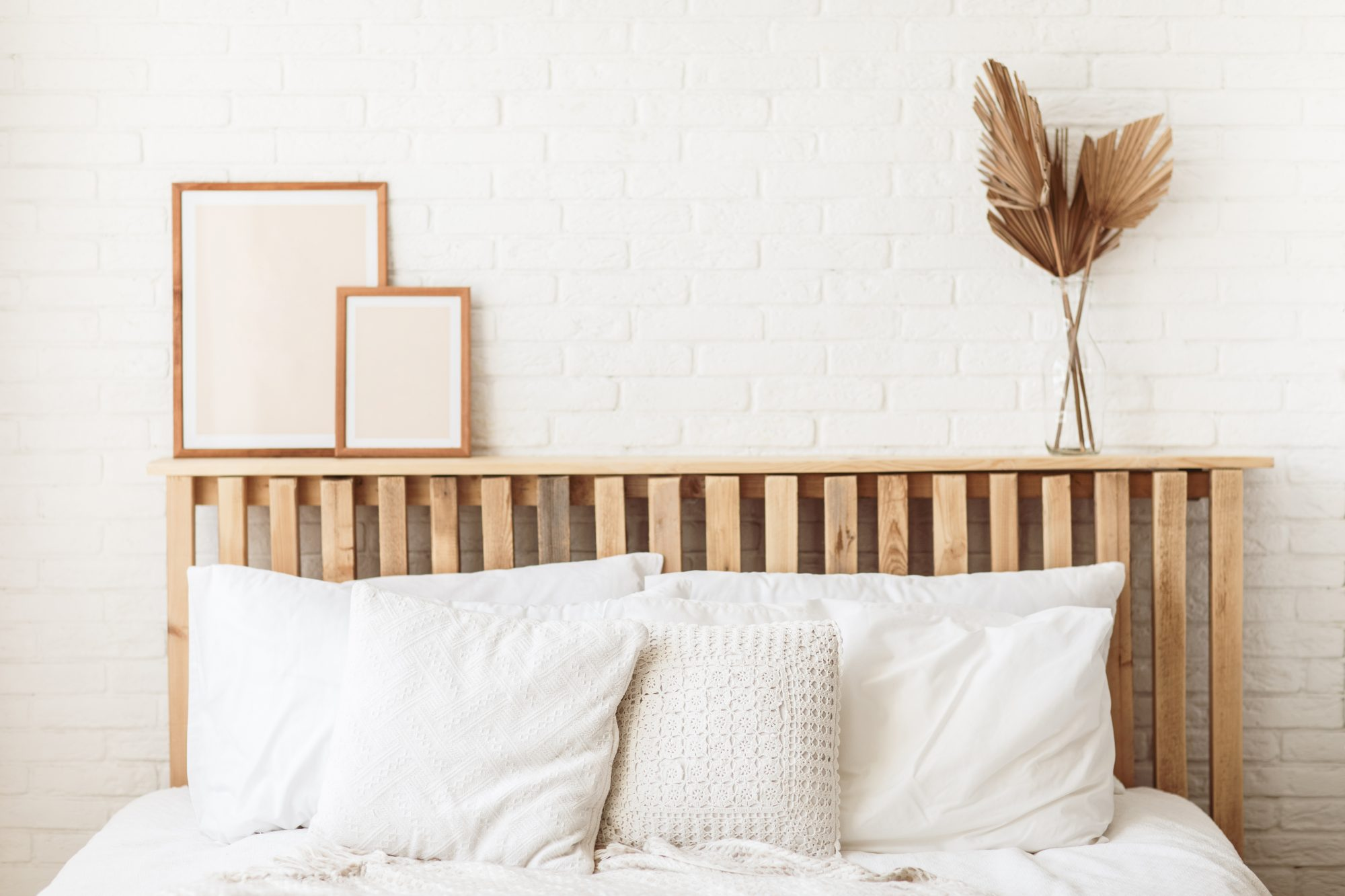 Wooden headboard with dry gold palm leaves in a glass vase