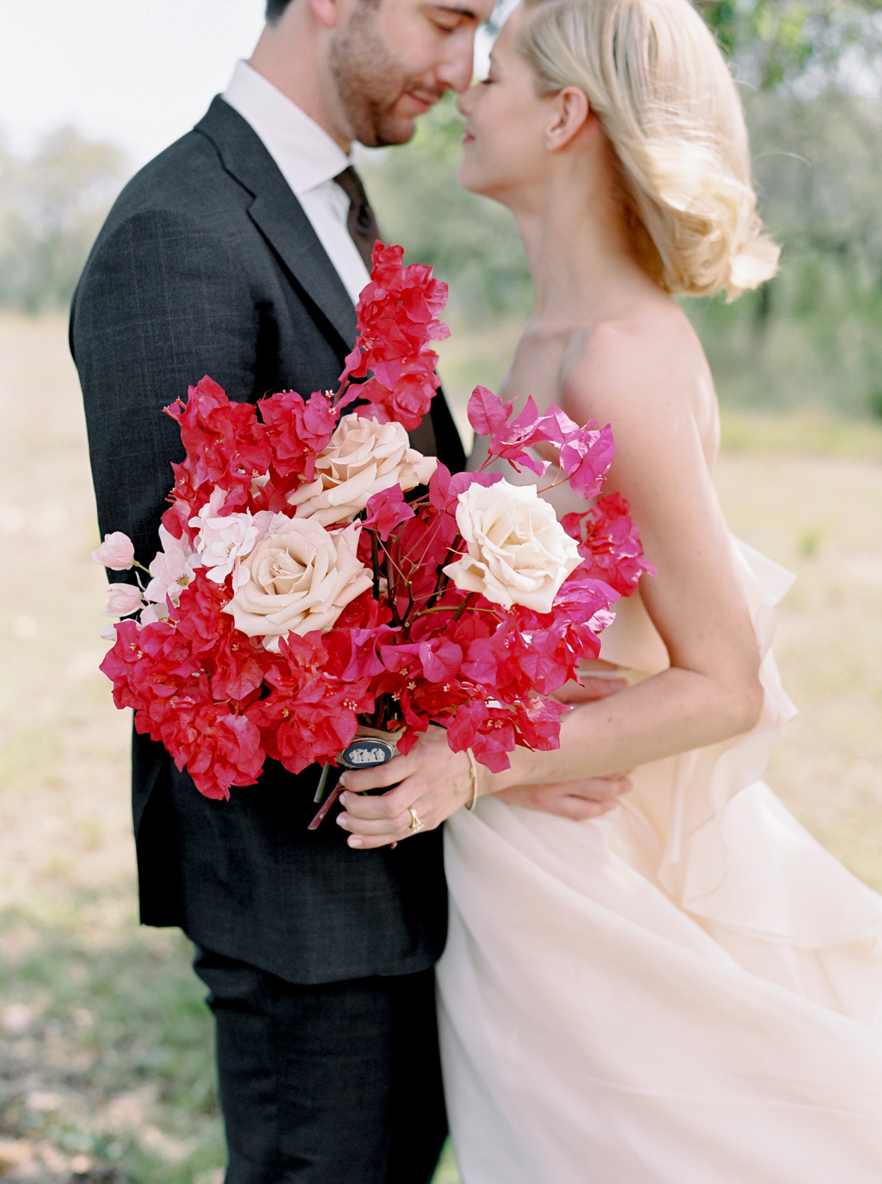 bride and groom with pink floral bouquet