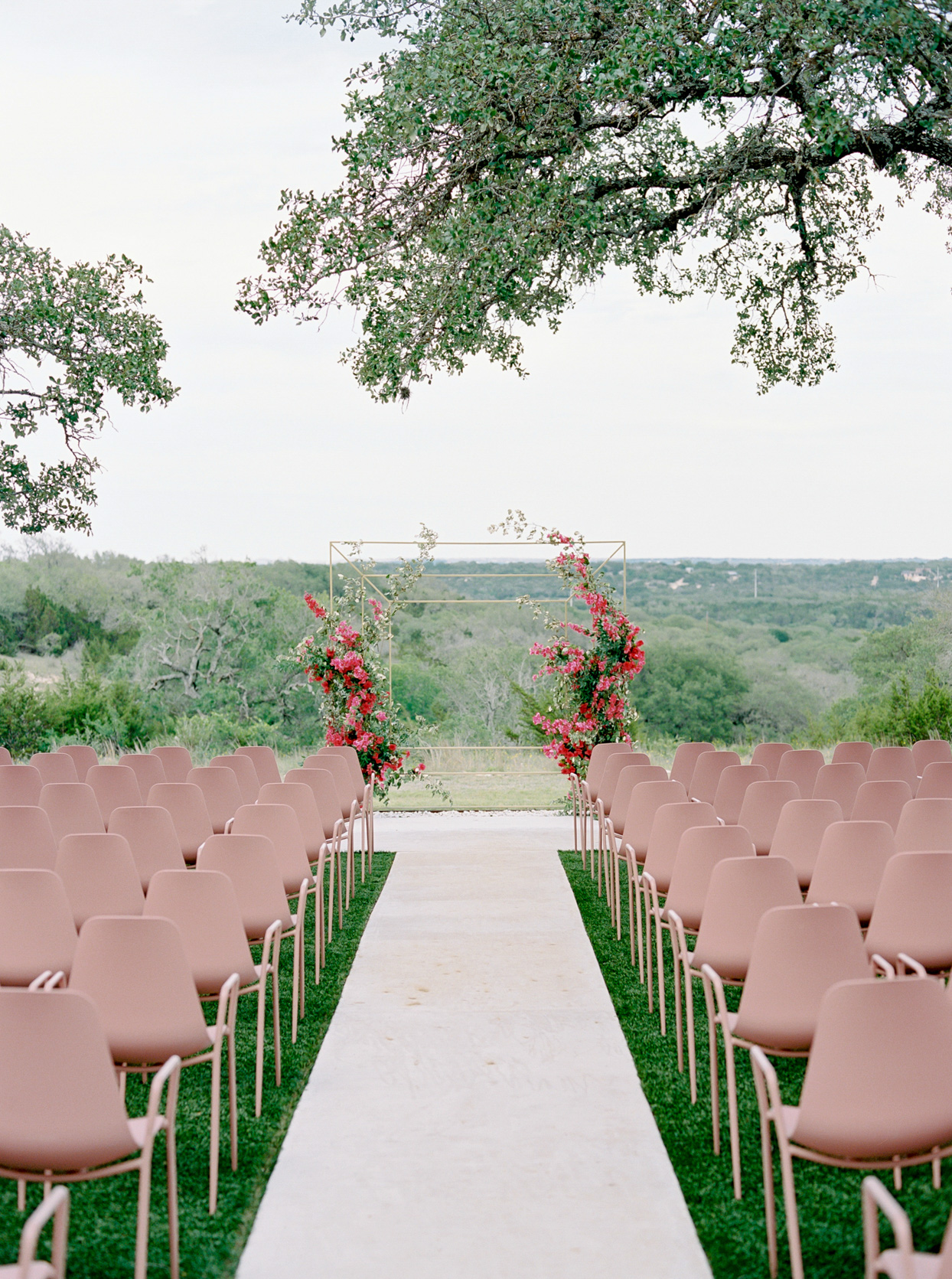 ceremony set up with blush chairs and floral archway at altar