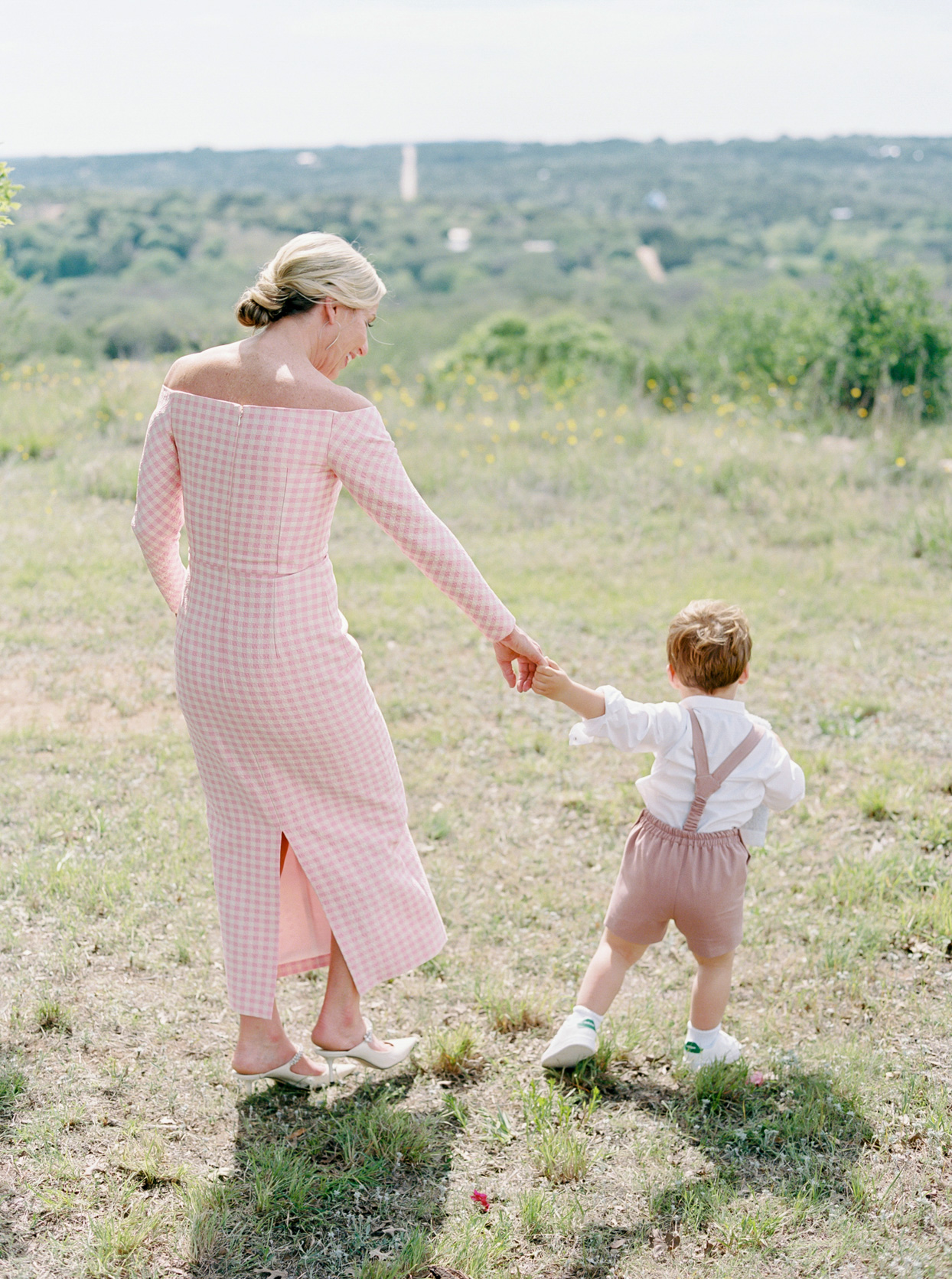 ring bearer wearing nude colored overalls and white shirt