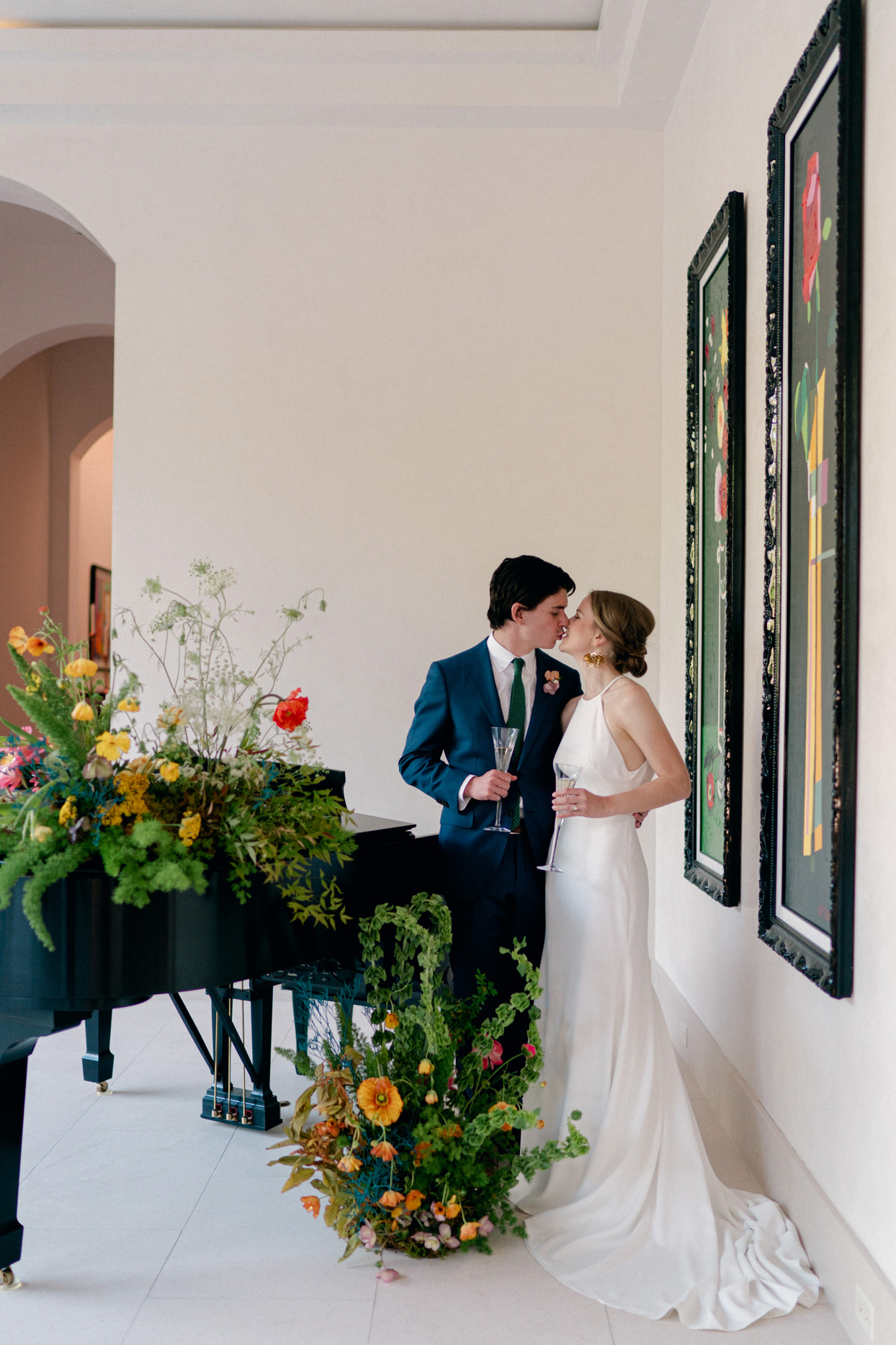 bride and groom kissing by piano