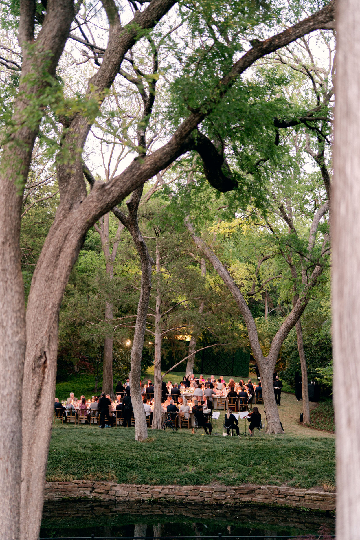 people sitting at outdoor tables for wedding reception