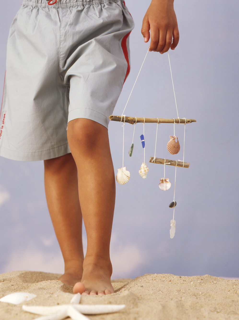child with shell wind chimes