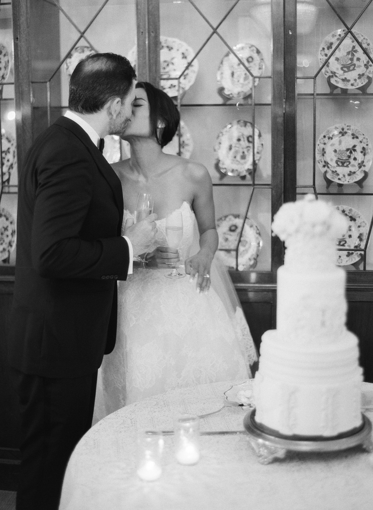 bride and groom kissing near cake during reception