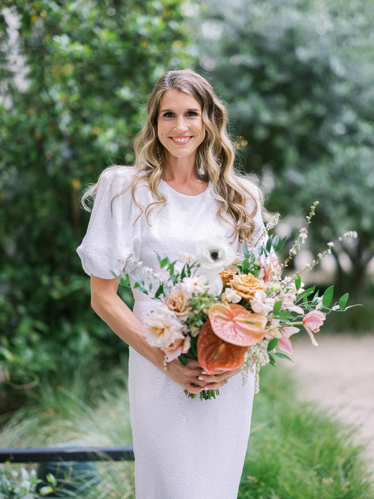 bride smiling holding bouquet of poppies roses and anthurium flowers