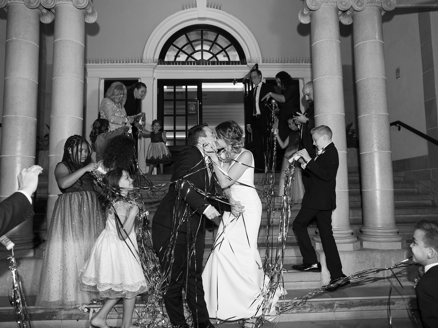 wedding couple kissing with guests popping streamers