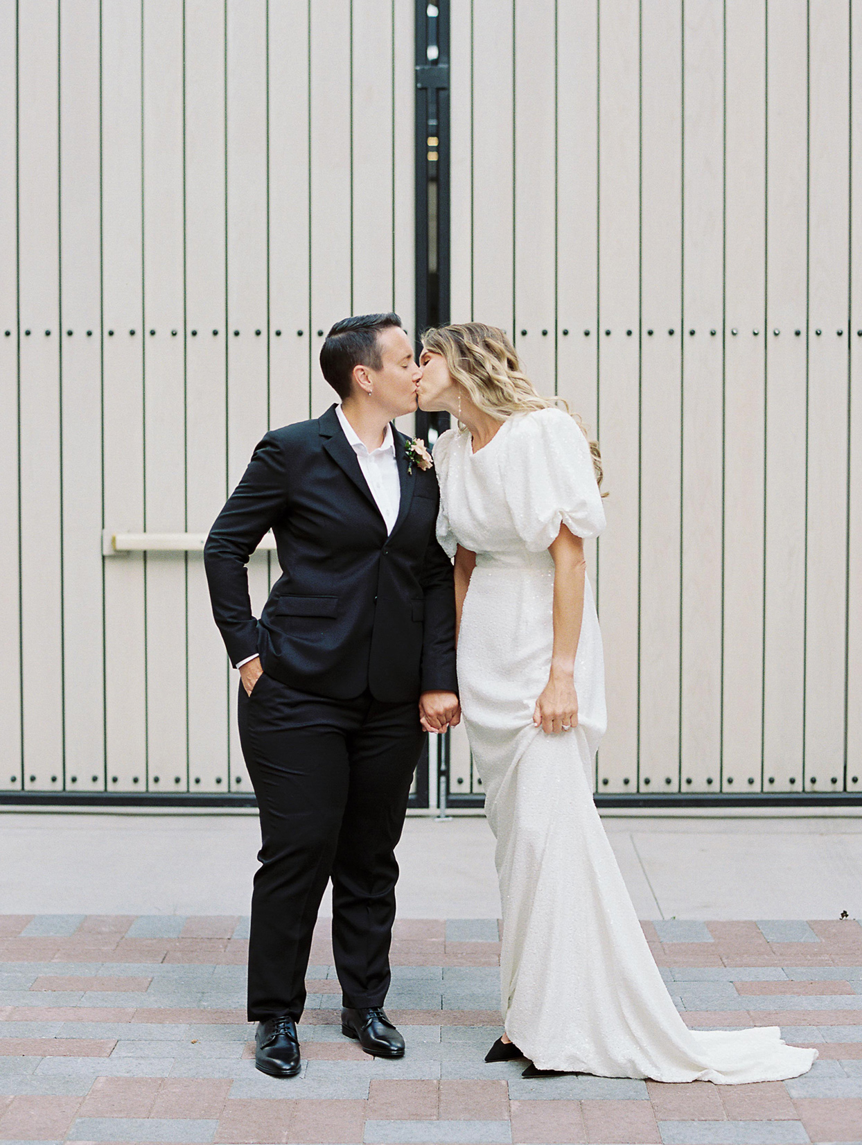 wedding couple holding hands and kissing