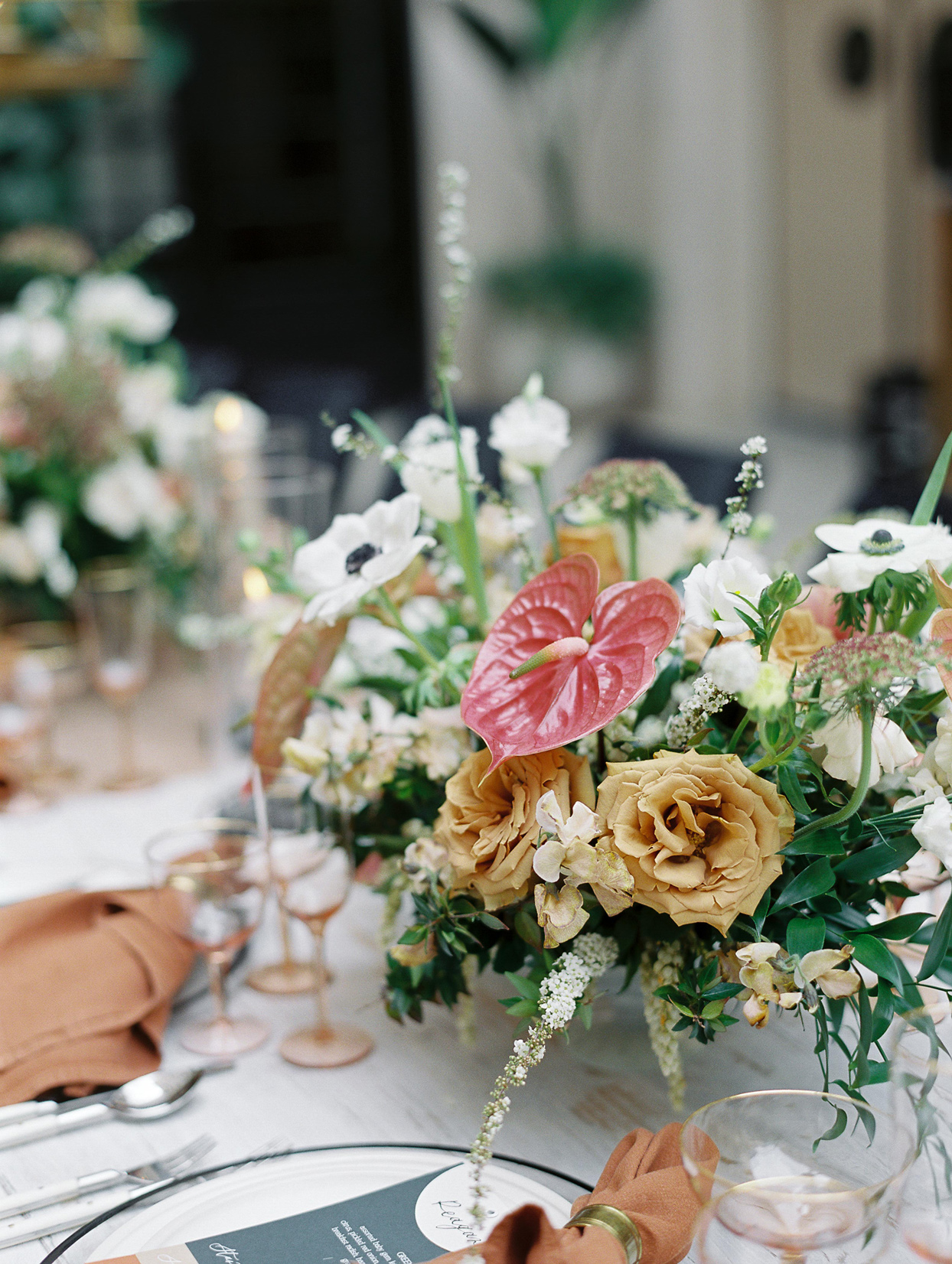 wedding reception centerpiece comprised of poppies roses and anthurium flowers